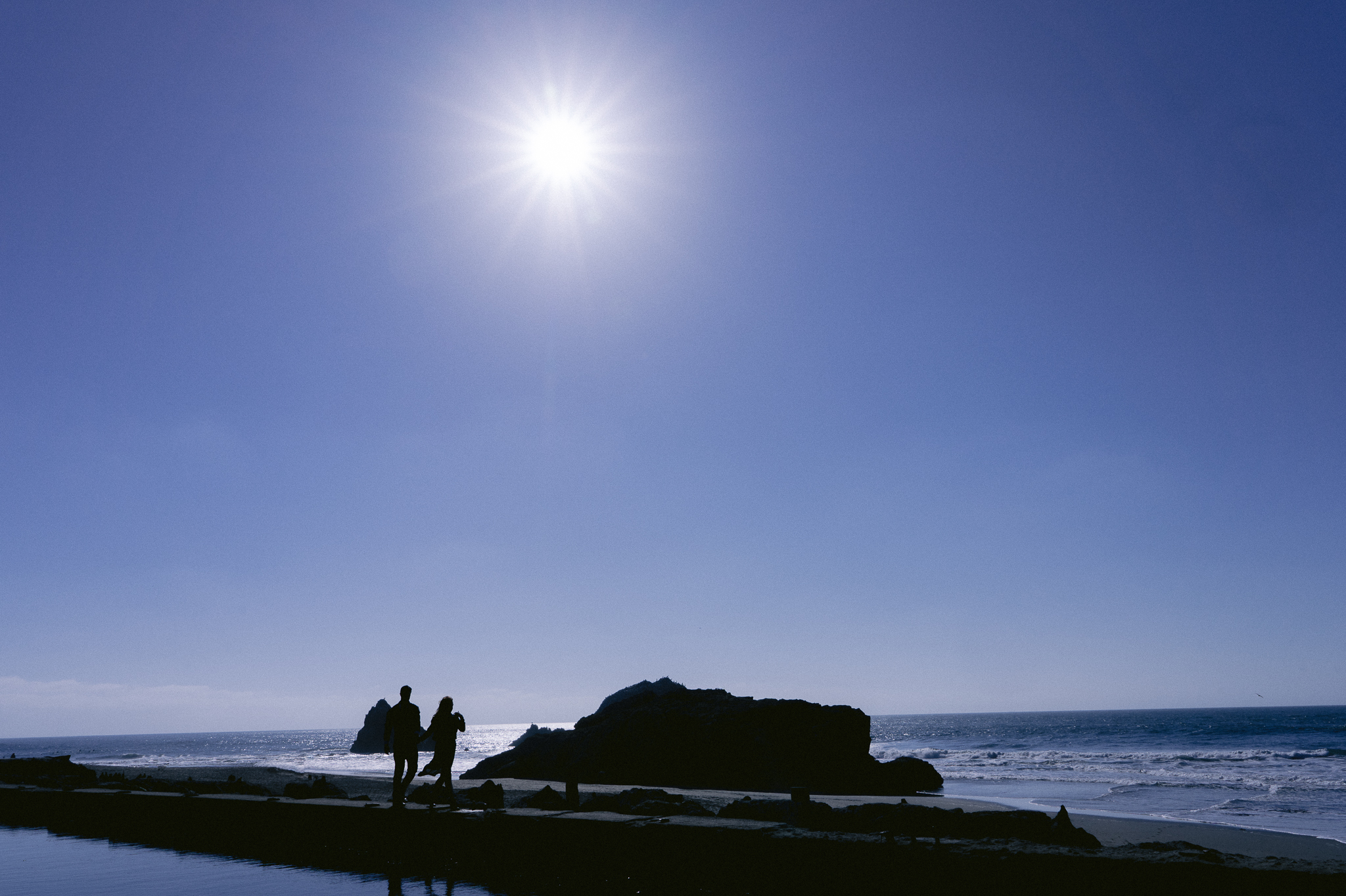 Backlit photo showing the shadow of an engaged couple walking hand in had along the Sutro Baths structure in San Francisco CA during their engagement session.