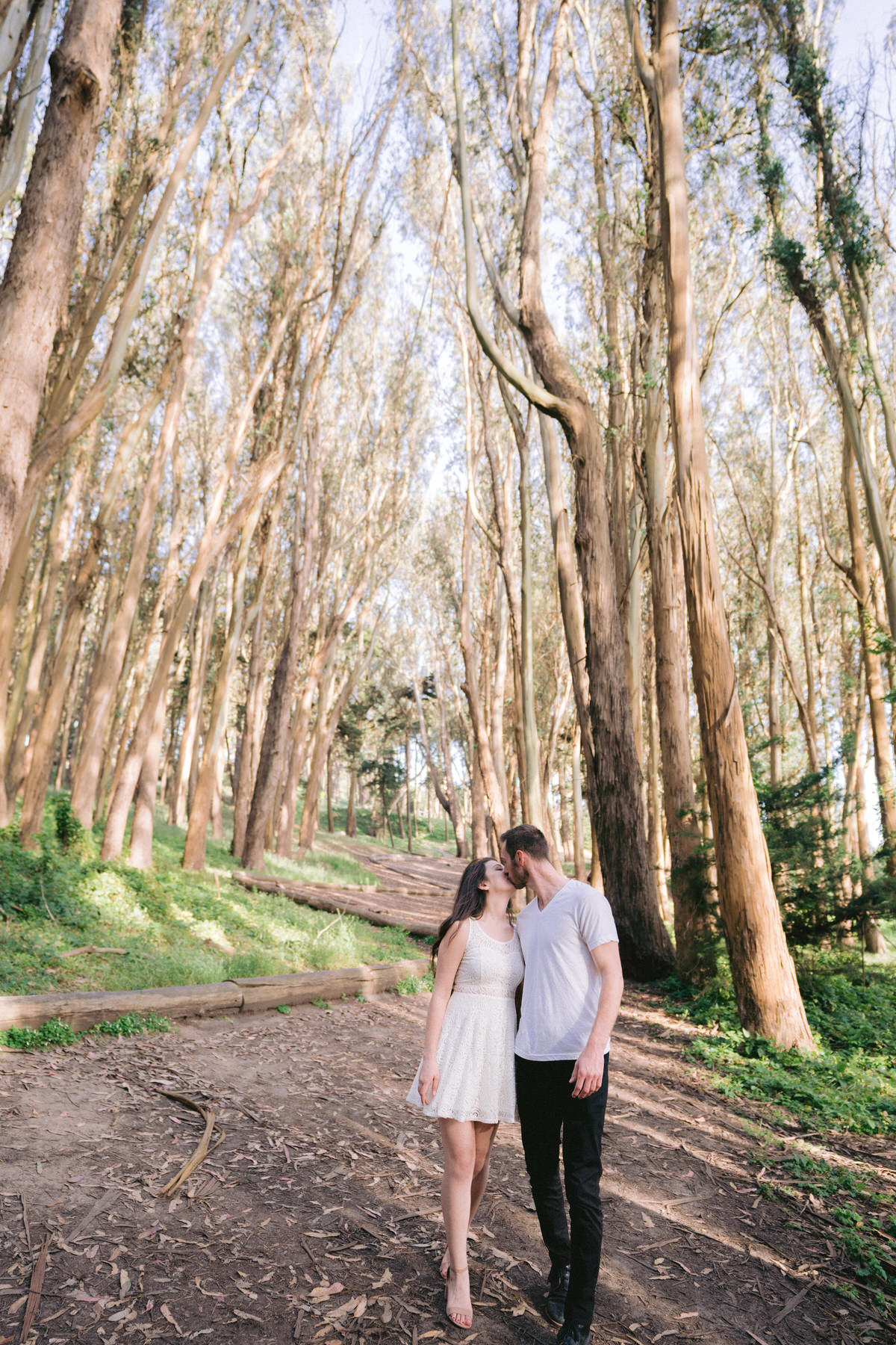 Engagement photo of a cute couple walking along Lovers Lane and kissing during their San Francisco engagement session.