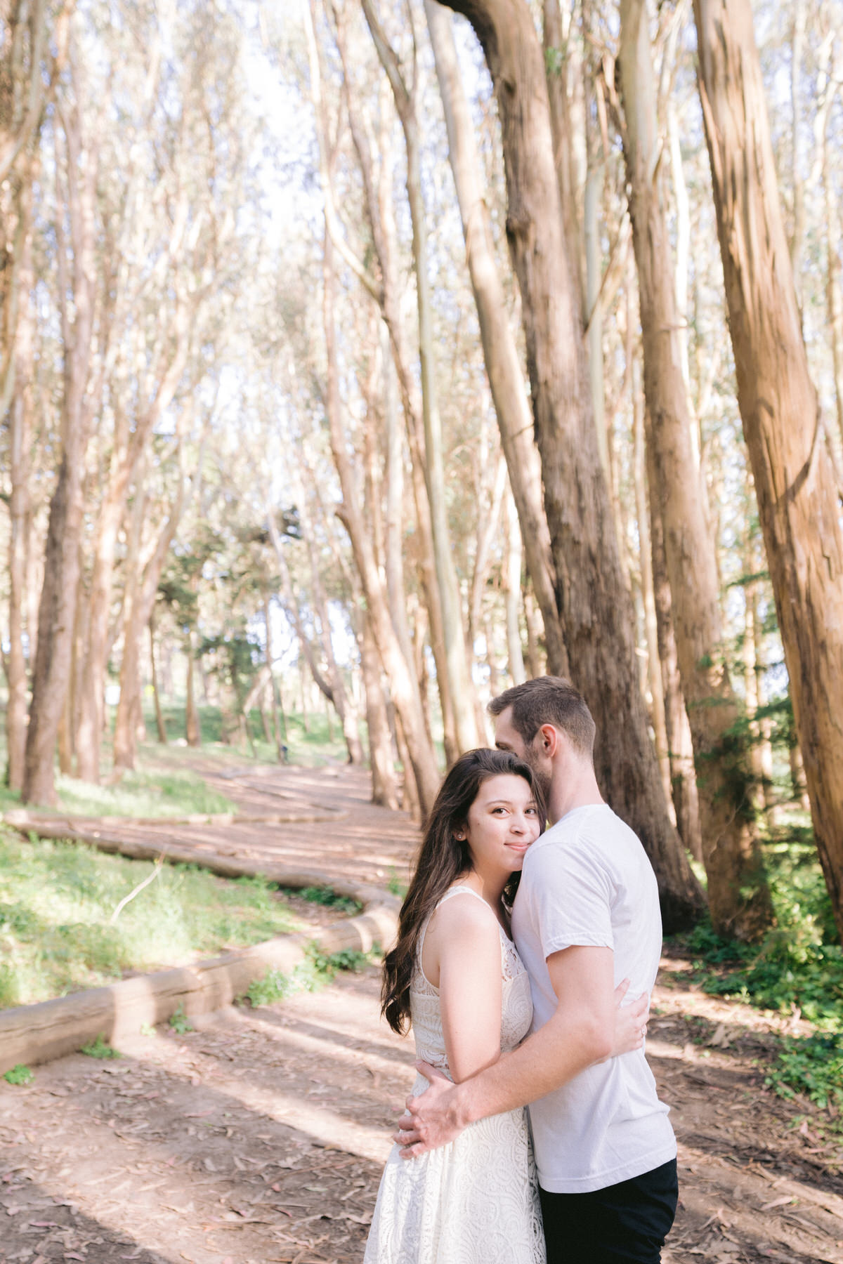 Couple embracing at Lovers lane trail in San Francisco during an engagement photo shoot.