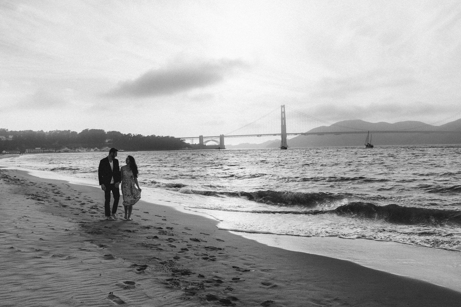 Engagement picture at Crissy Field beach with couple embracing romatically on the beach with Golden Gate bridge in the background as the sun is setting.