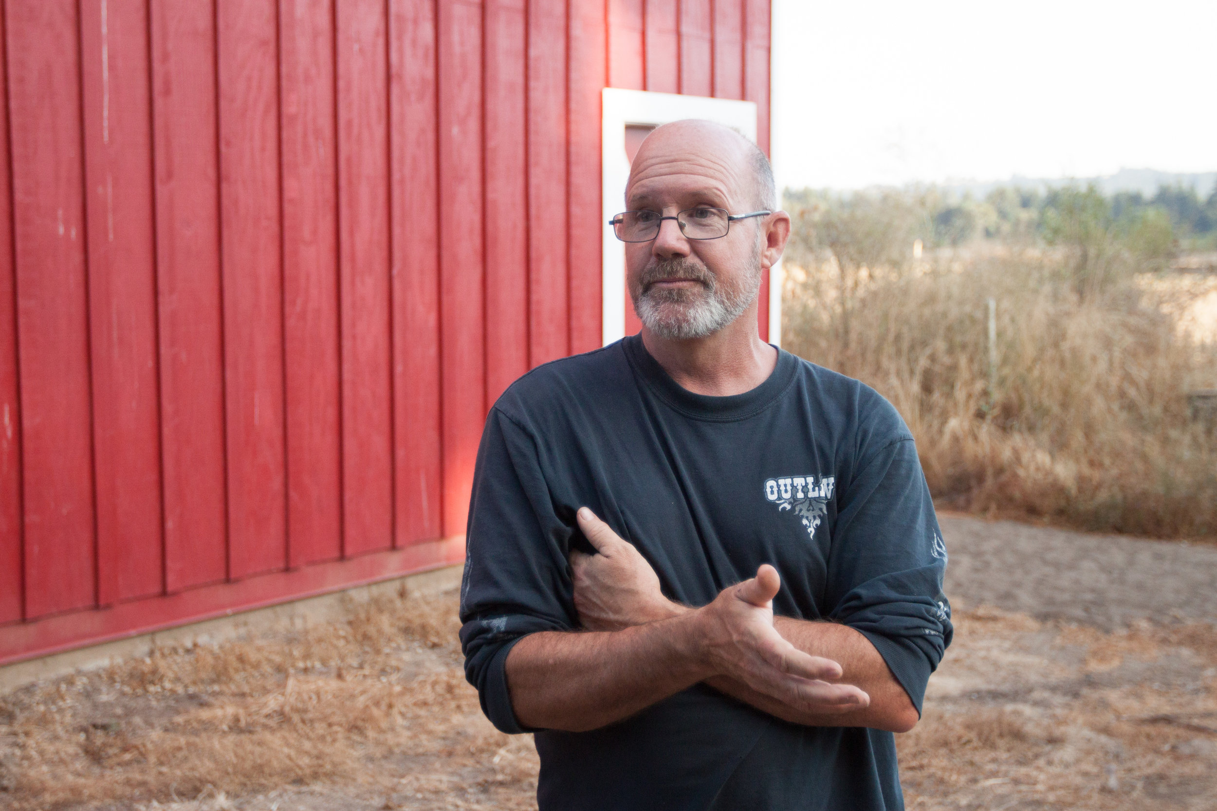 Michael O'Loughlin, owner and operator on the farm standing near his barn built in 1937.