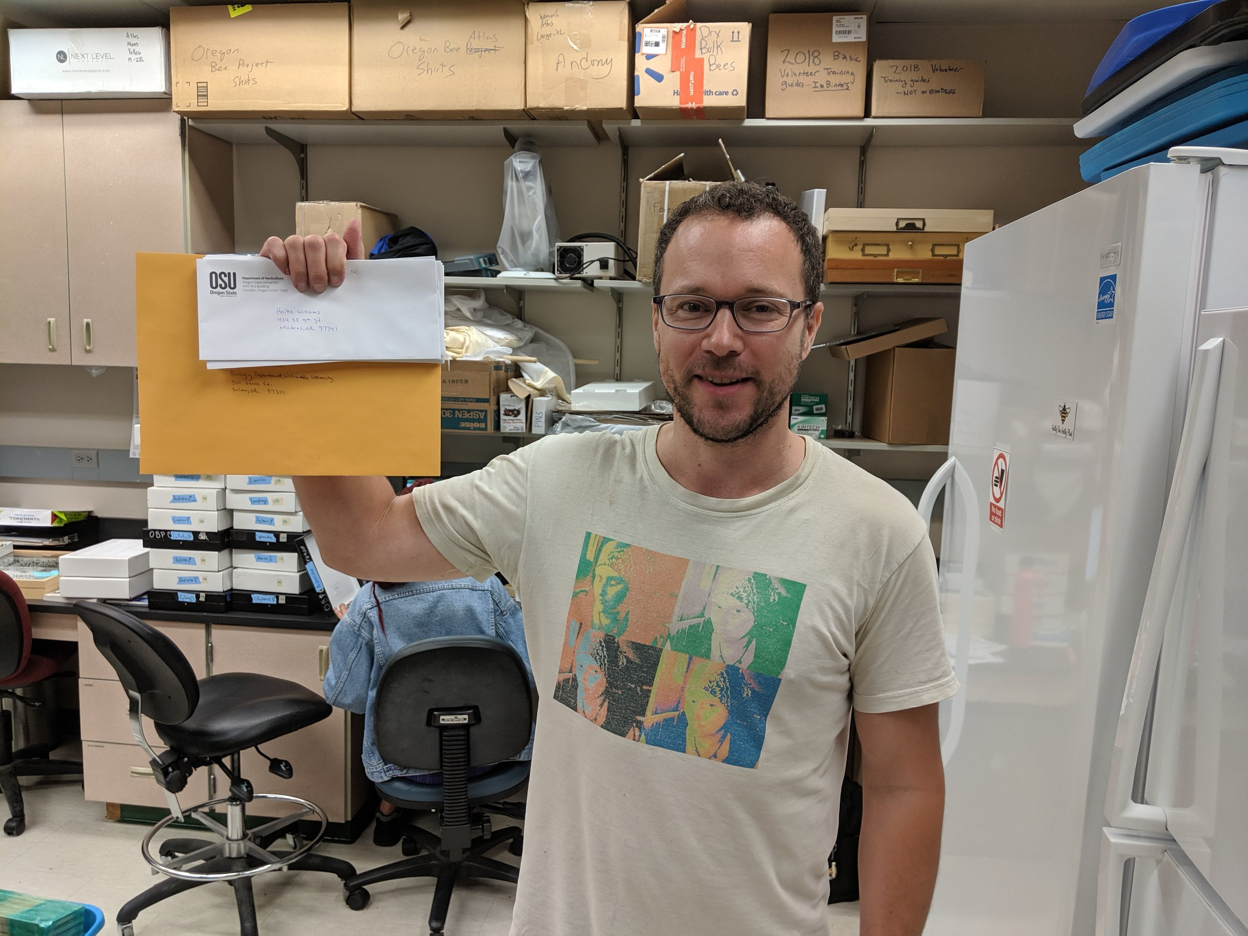 Cody Feurborn with stack of insect labels he is mailing out to you (Umayyah is behind him pinning up bees from the nest blocks). Cody and Umayyah head back to class in September. Make sure to get your records to them by this date.