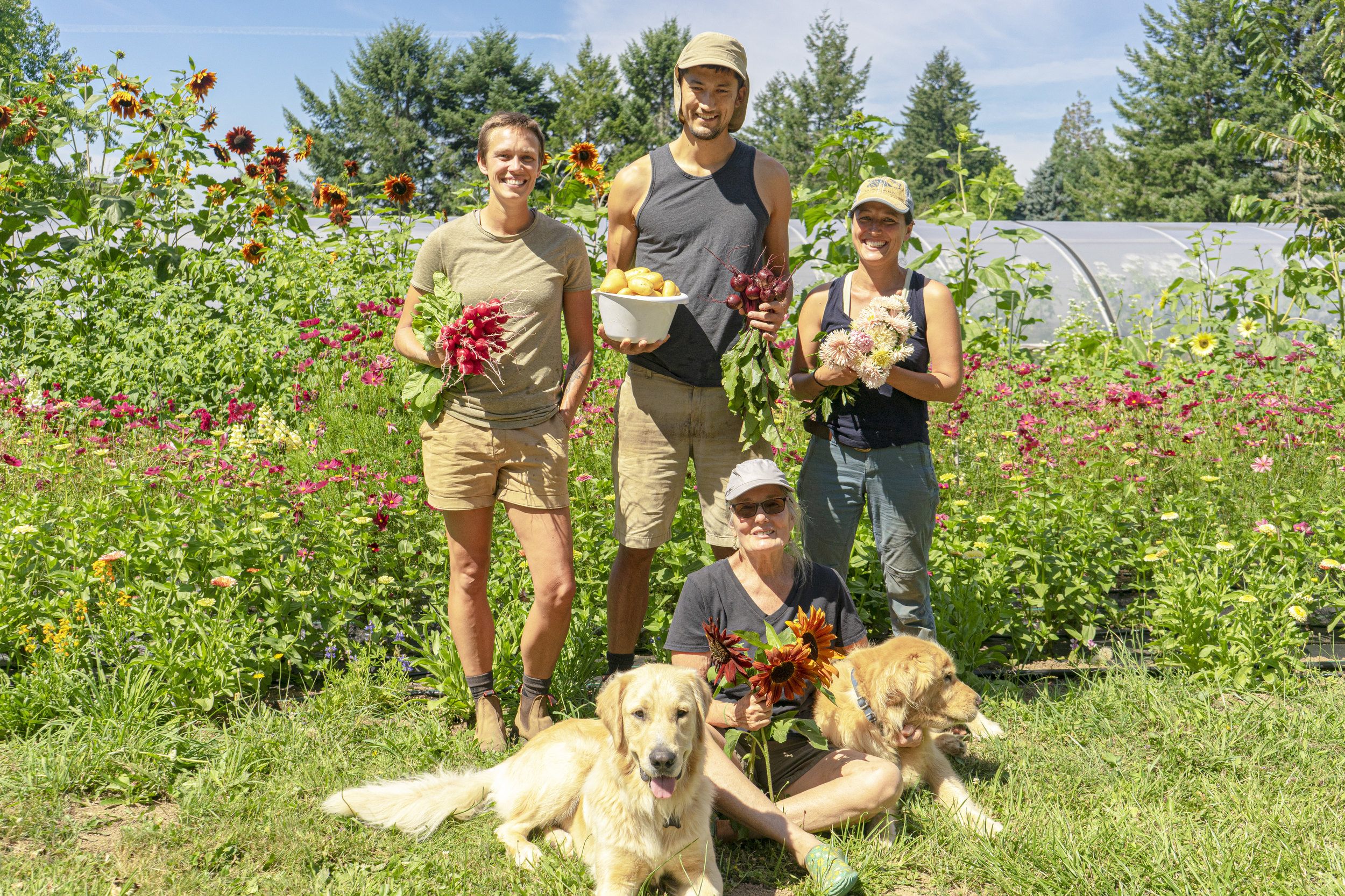 Brindley, Spencer, Jennie, and Pam posing with fresh goods from their farm. (Left to Right)