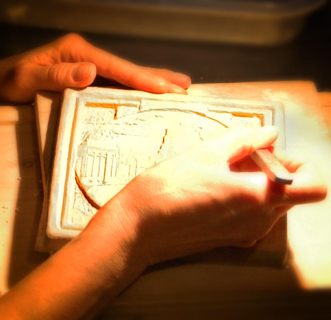 artist Tonya Lutz sculpts a new tile design by hand.