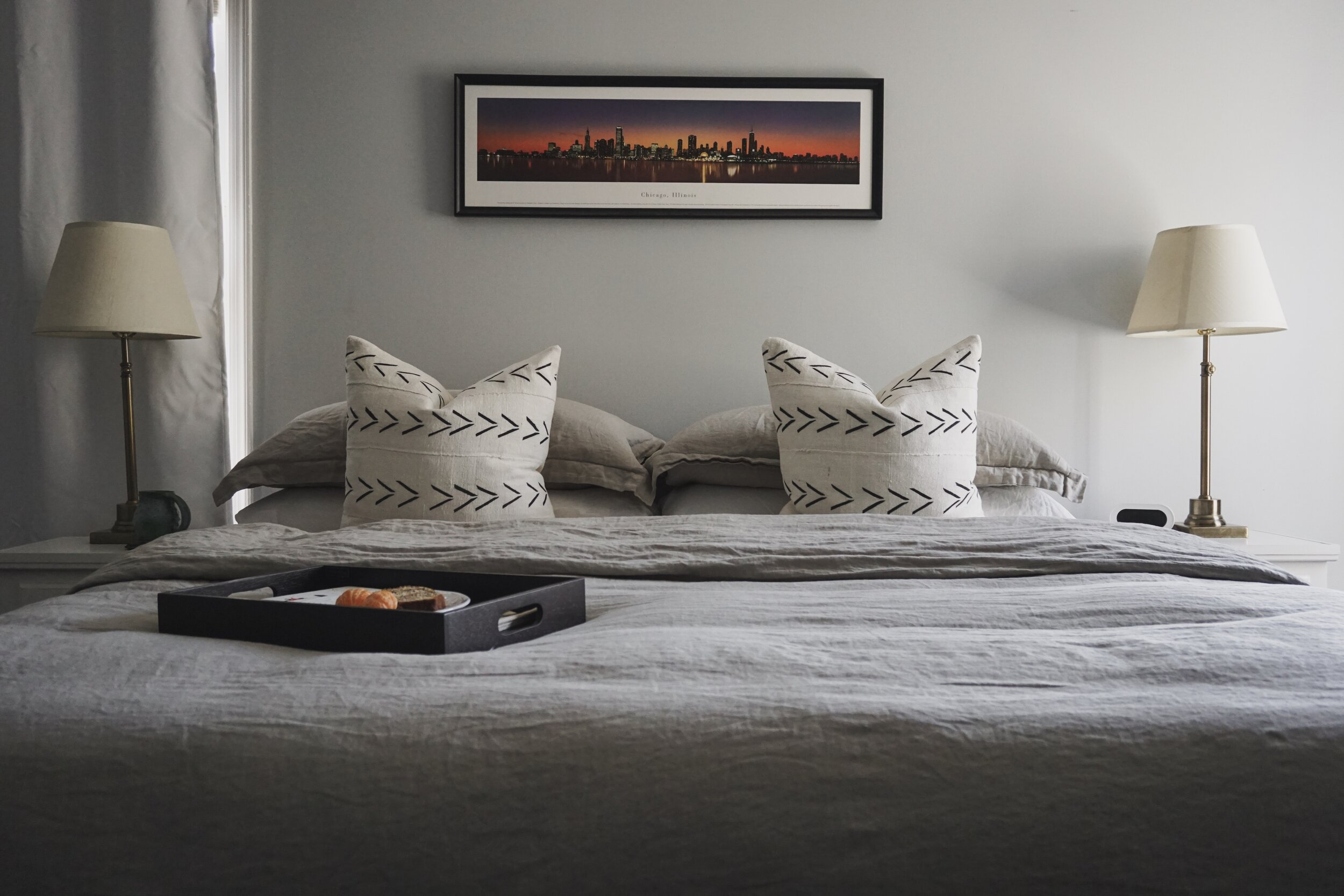 When we upgraded to a king bed we chose a linen duvet cover with bamboo sheets and African mud-cloth throw pillows. The lamps and nightstands were handed down from my grandmother. We haven't gotten an actual bed yet because the four-poster I want won't fit underneath the ceiling fan. #renterproblems