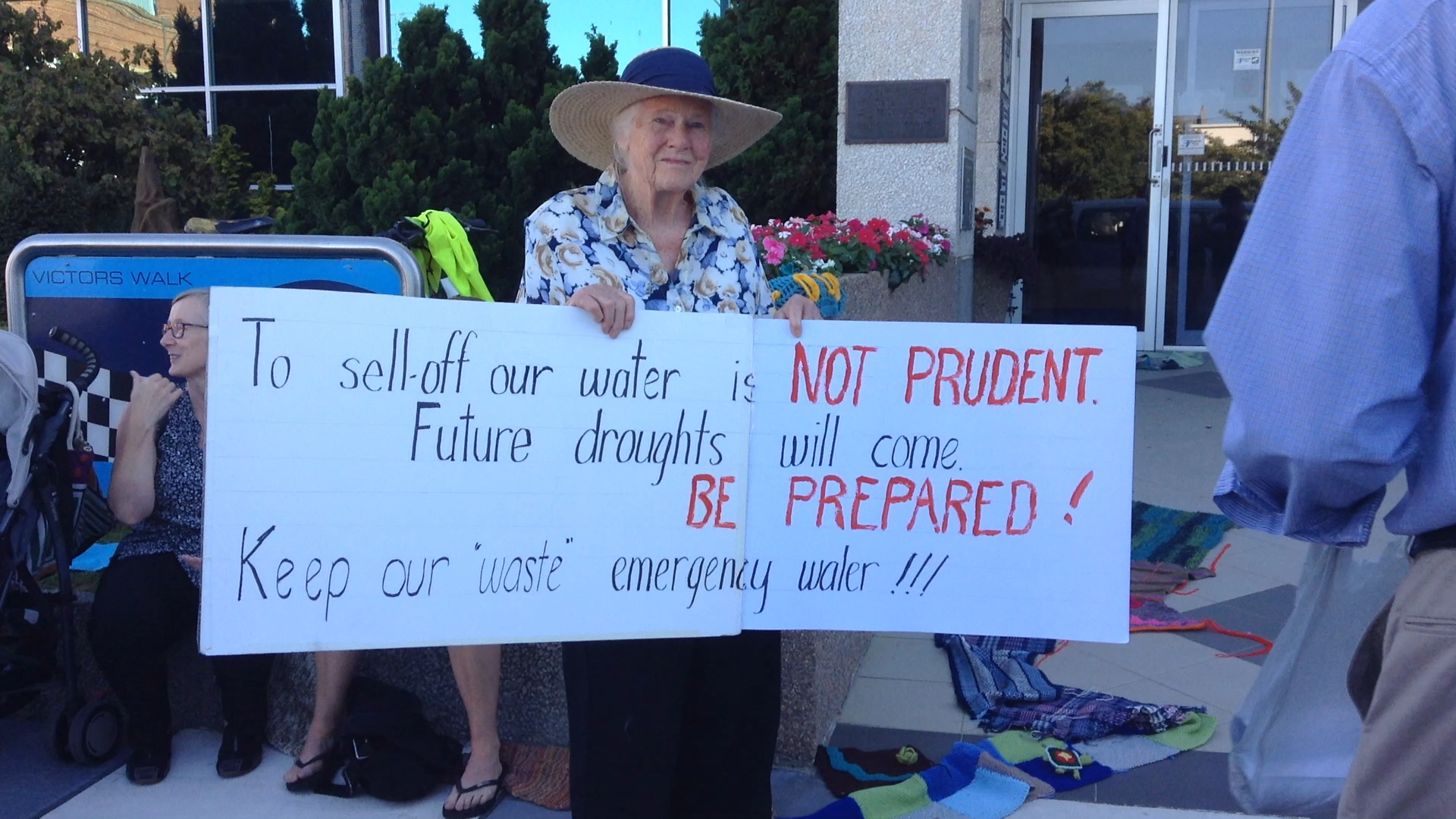 Isabel Higgins with a hand-written sign outside council chambers, Feb 2016. The yarned river can be seen snaking towards the door of council chambers. Photo by Tracy Sorensen.
