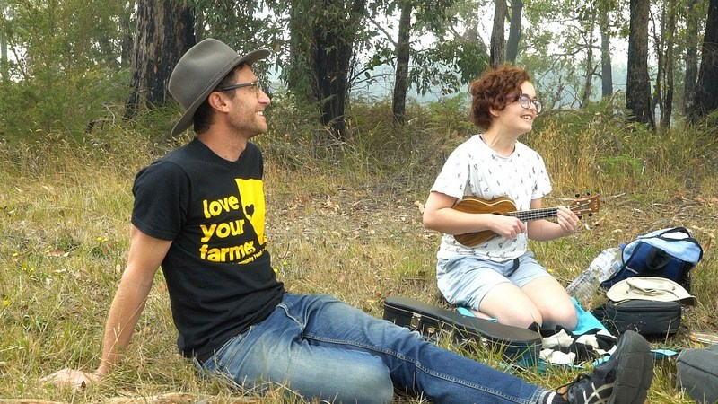 """Roo Bramley (right) gives a rousing rendition of """"Three Acres and a Cow"""" at the Hallora Recreation Reserve."""