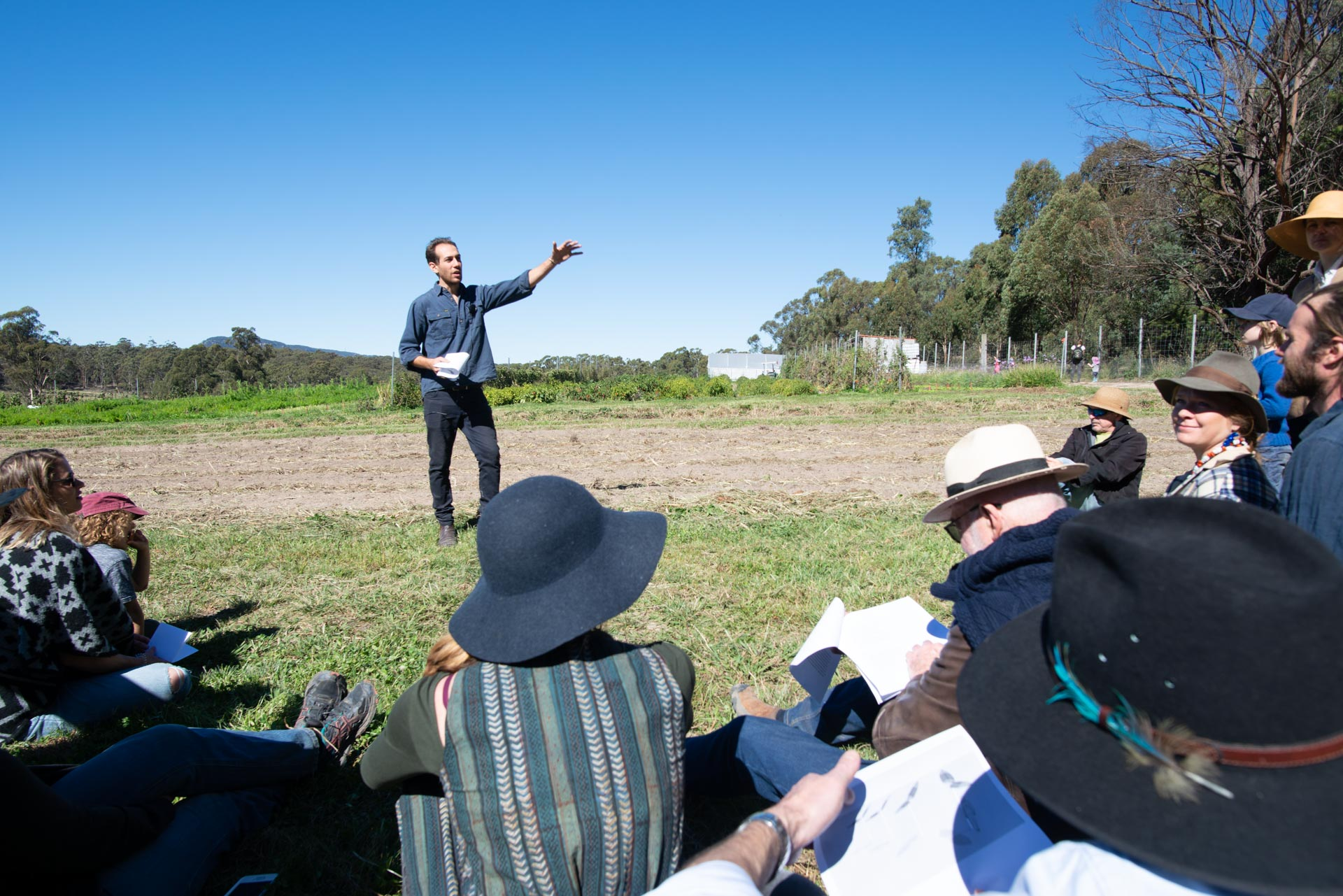 Artist Mark Swartz is seen here speaking in front of the patch of the market garden which has been allocated to 'the solar garden' project. He, Erika and Hayden and solar scientist Bjorn Sturmberg, are nutting out how solar-panelled sculptures or 'trees' could be installed here. They could function as a 'storey', harvesting sunlight to power things like irrigation pumps, while also providing modest shade to other plants.