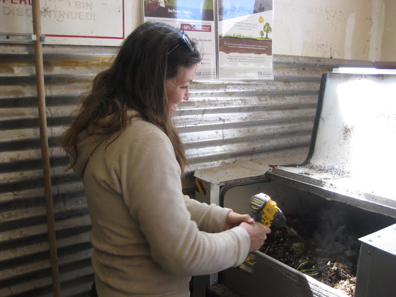 Ophir resident Jacey Depriest stirs the compost with a drill auger. [Photo by Katie Klingsporn]
