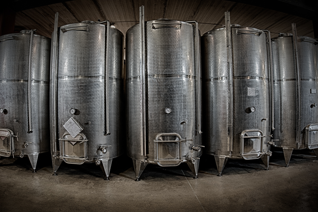 INSIDE THE CELLAR, IN THE WINEMAKING ROOMS, A BATTERY OF CONTROLLED VATS AND PUMPS FOR PUMPING UP,