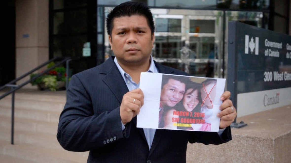 Lowell Menorca holds a photo he says was left on his car in the Philippines showing his family with a red 'X' through the face of his then-two-year-old daughter and the warning, 'Say Goodbye.' He fled the country and sought refugee status in Canada.(Gavin Fisher/CBC)