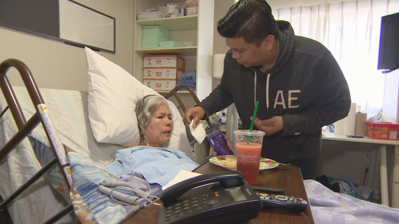 Lowell Menorca cares for his mother, Fredisminda Menorca, partially paralyzed by a stroke shortly after she applied for refugee status in Canada.(Harold Dupuis/CBC)