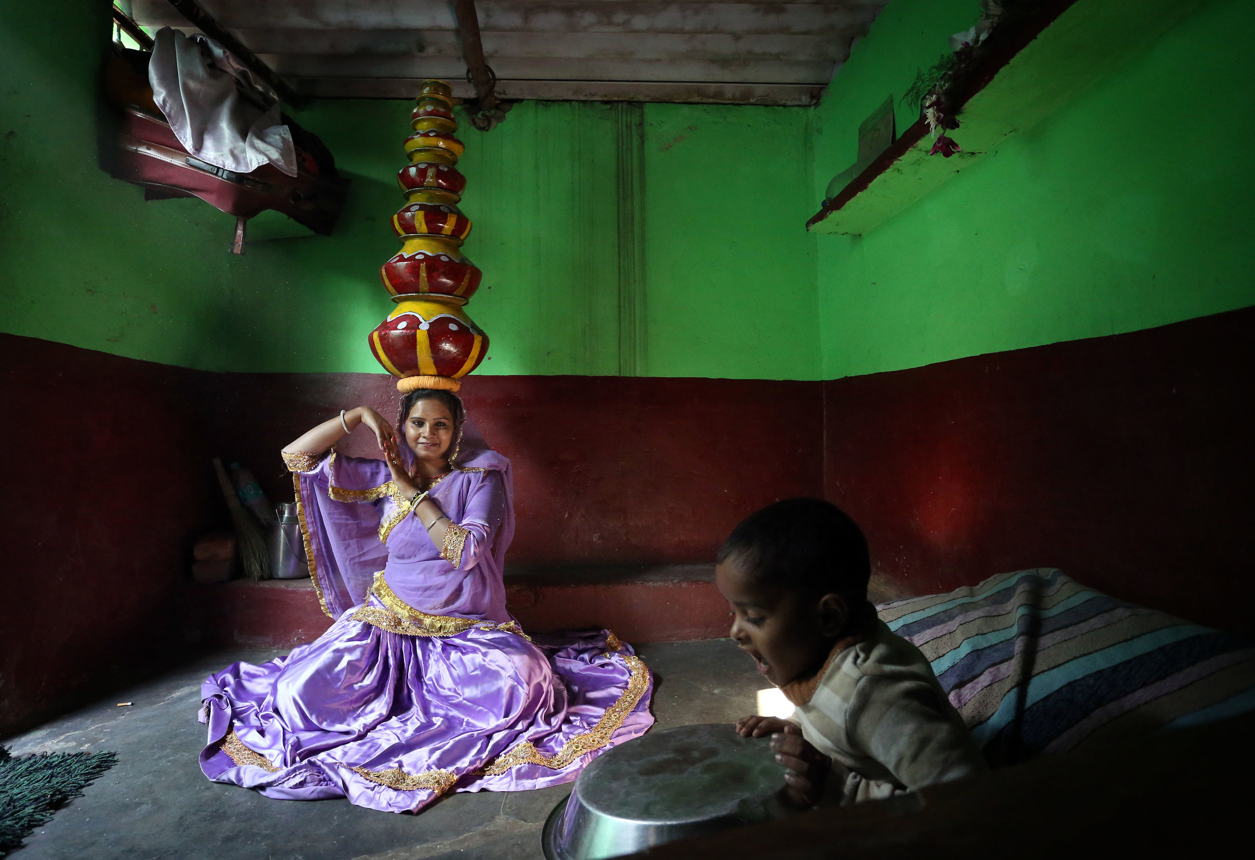 Bhavai dancer Arti Bhatt, practises the traditional Rajasthani folk dance balancing pots on her head alongside her son at their home in the Kathputli slum colony of New Delhi, India, December 7th, 2014. She is one of 40,000 people living in the slum, which is popularly known for being the worlds largest colony of street performers, including magicians, snake charmers, acrobats, singers, dancers, actors, traditional healers and musicians and puppeteers. Their livelihood is under threat however as the Delhi government has obtained contracts to demolish the colony to make way for developers to build high-rise apartments. Photo Credit: Susannah Ireland