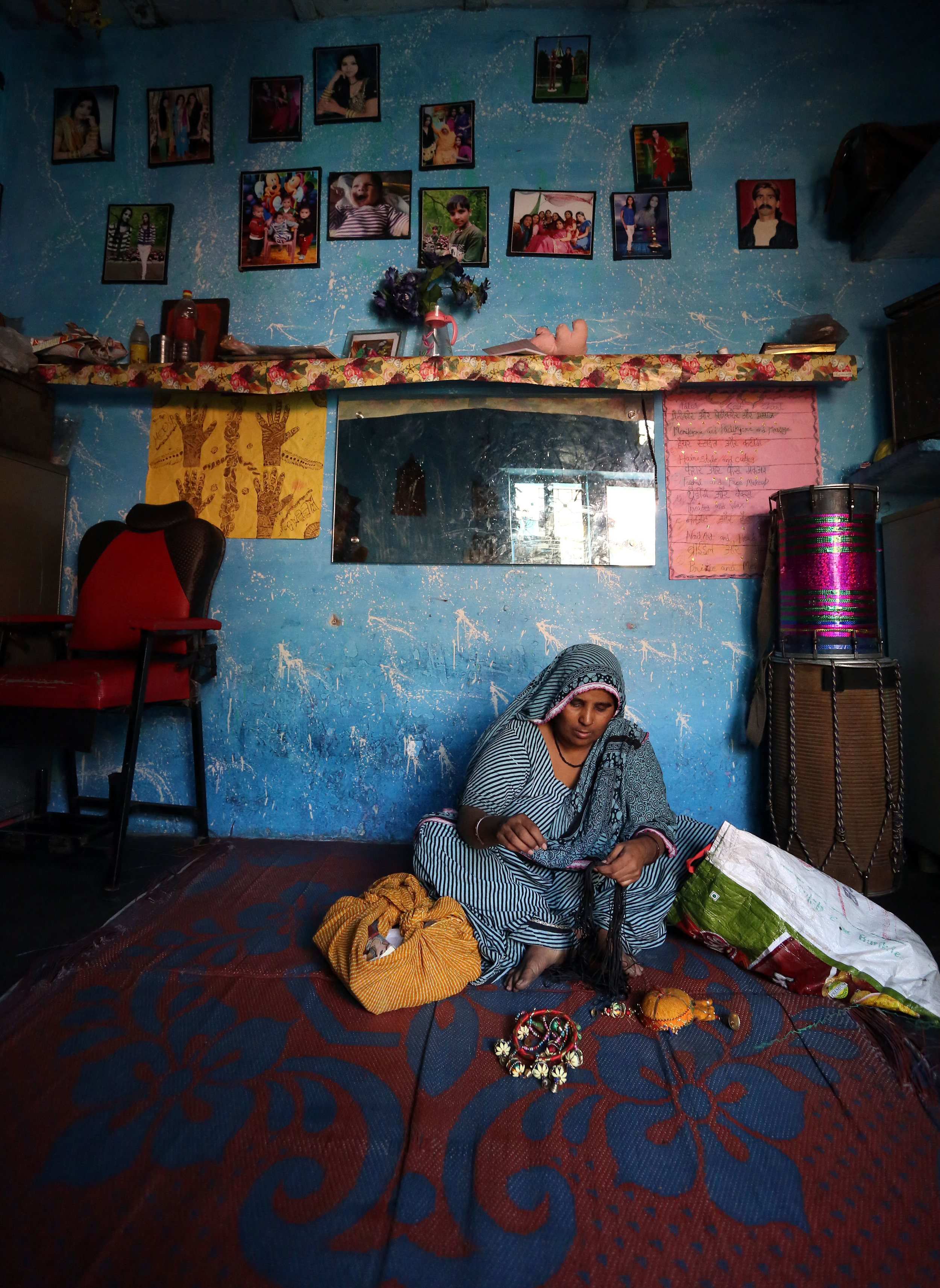 Mother-of-seven Mitoo Bhatt is pictured making traditional Rajasthani canopy hangings, used as good luck charms, at her home in the Kathputli slum colony of New Delhi, India, December 7th, 2014. She is one of 40,000 people living in the slum, which is popularly known for being the worlds largest colony of street performers, including magicians, snake charmers, acrobats, singers, dancers, actors, traditional healers and musicians and puppeteers. Their livelihood is under threat however as the Delhi government has obtained contracts to demolish the colony to make way for developers to build high-rise apartments.