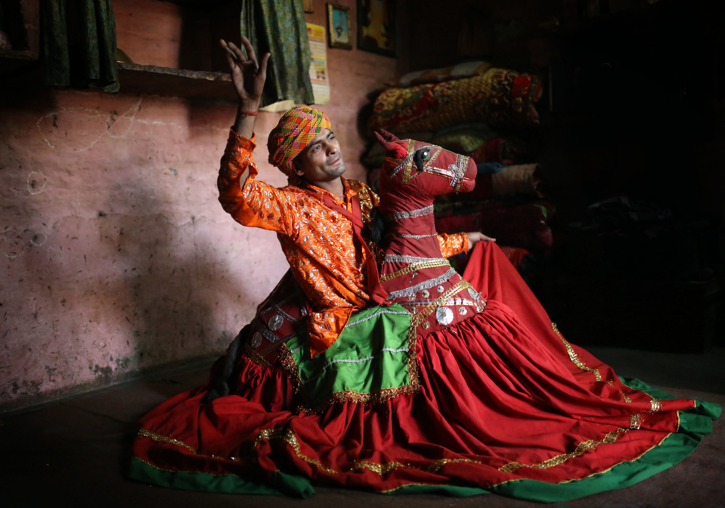 Jagdeesh Makkhan is pictured performing the Kachhi Ghodi traditional Rajasthani folk dance at his home in the Kathputli slum colony of New Delhi, India, December 7th, 2014. He is one of 40,000 people living in the slum, which is popularly known for being the worlds largest colony of street performers,a including magicians, snake charmers, acrobats, singers, dancers, actors, traditional healers and musicians and puppeteers. Their livelihood is under threat however as the Delhi government has obtained contracts to demolish the colony to make way for developers to build high-rise apartments.