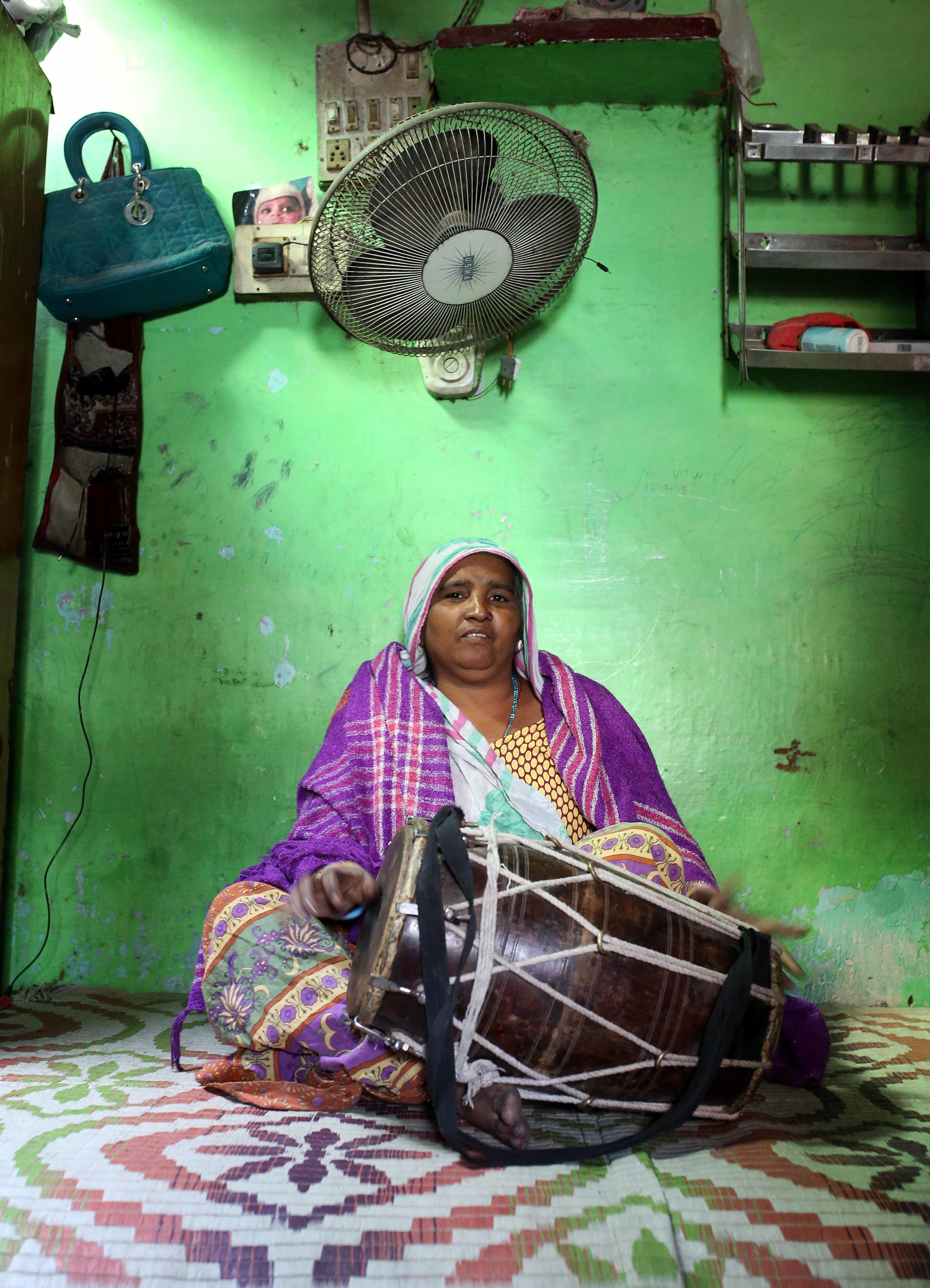 Kamla Bhatt, mother of Aarti, is pictured singing and playing the drums at her home in the Kathputli slum colony of New Delhi, India, December 7th, 2014. She is one of 40,000 people living in the slum, which is popularly known for being the worlds largest colony of street performers, including magicians, snake charmers, acrobats, singers, dancers, actors, traditional healers and musicians and puppeteers. Their livelihood is under threat however as the Delhi government has obtained contracts to demolish the colony to make way for developers to build high-rise apartments.