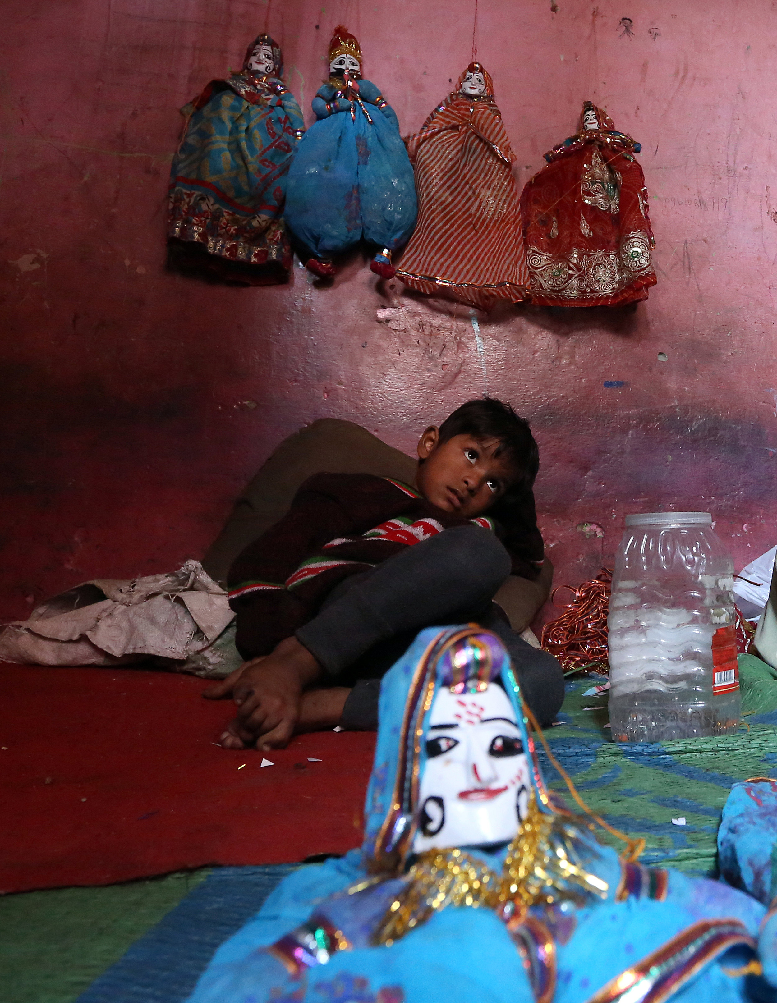 A boy is pictured underneath the puppets his mother, Rajasthani puppet maker Ghita Devi, made at his home in the Kathputli slum colony of New Delhi, India, December 8th, 2014. She is one of 40,000 people, speaking 11 different languages, living in the slum, which is popularly known for being the worlds largest colony of street performers, including magicians, snake charmers, acrobats, singers, dancers, actors, traditional healers and musicians and puppeteers. Their livelihood is under threat however as the Delhi government has obtained contracts to demolish the colony to make way for developers to build high-rise apartments.