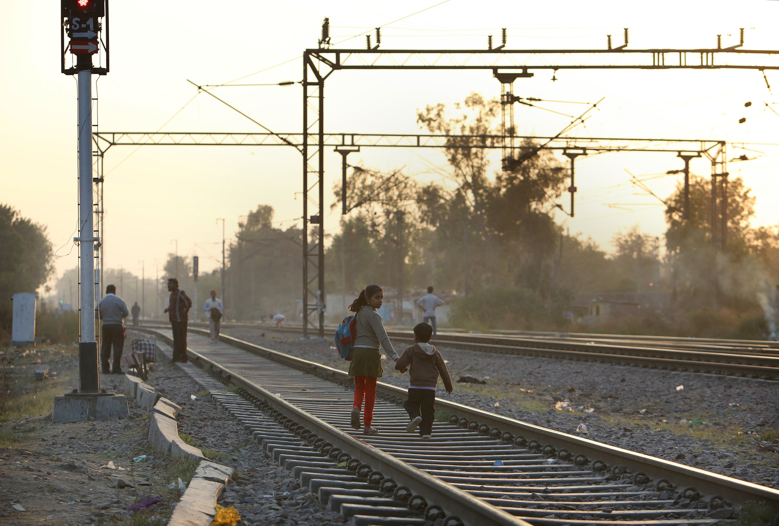 Children walk home on the railway track which runs alongside the Kathputli slum colony of New Delhi, India, December 10th, 2014. 40,000 people live in the slum, speaking 11 different languages, which is popularly known for being the worlds largest colony of street performers, including magicians, snake charmers, acrobats, singers, dancers, actors, traditional healers and musicians and puppeteers. Their livelihood is under threat however as the Delhi government has obtained contracts to demolish the colony to make way for developers to build high-rise apartments.