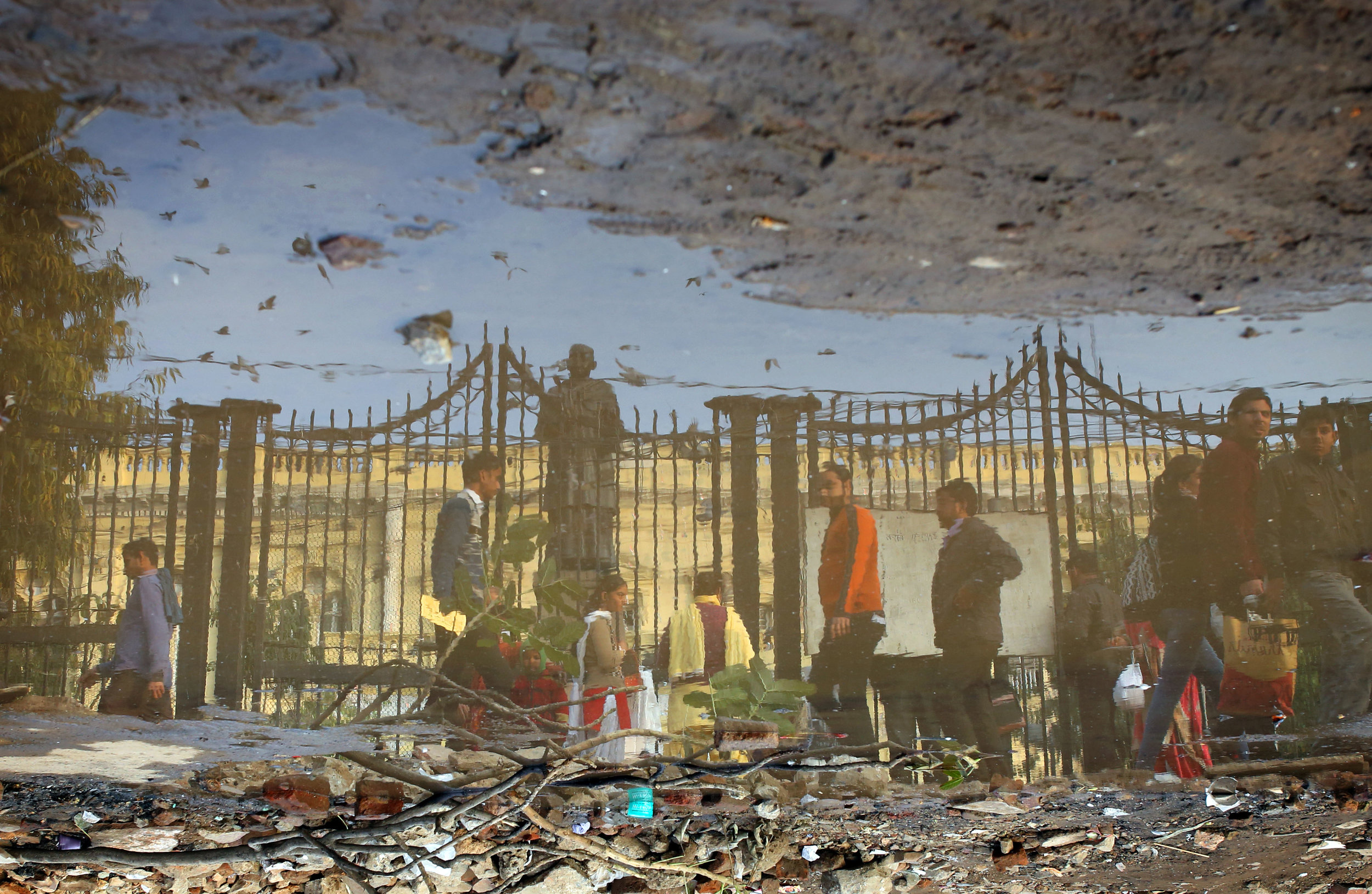 Passers by are pictured reflected in a puddle outside the Gandhi Memorial at Old Delhi's Town Hall, India