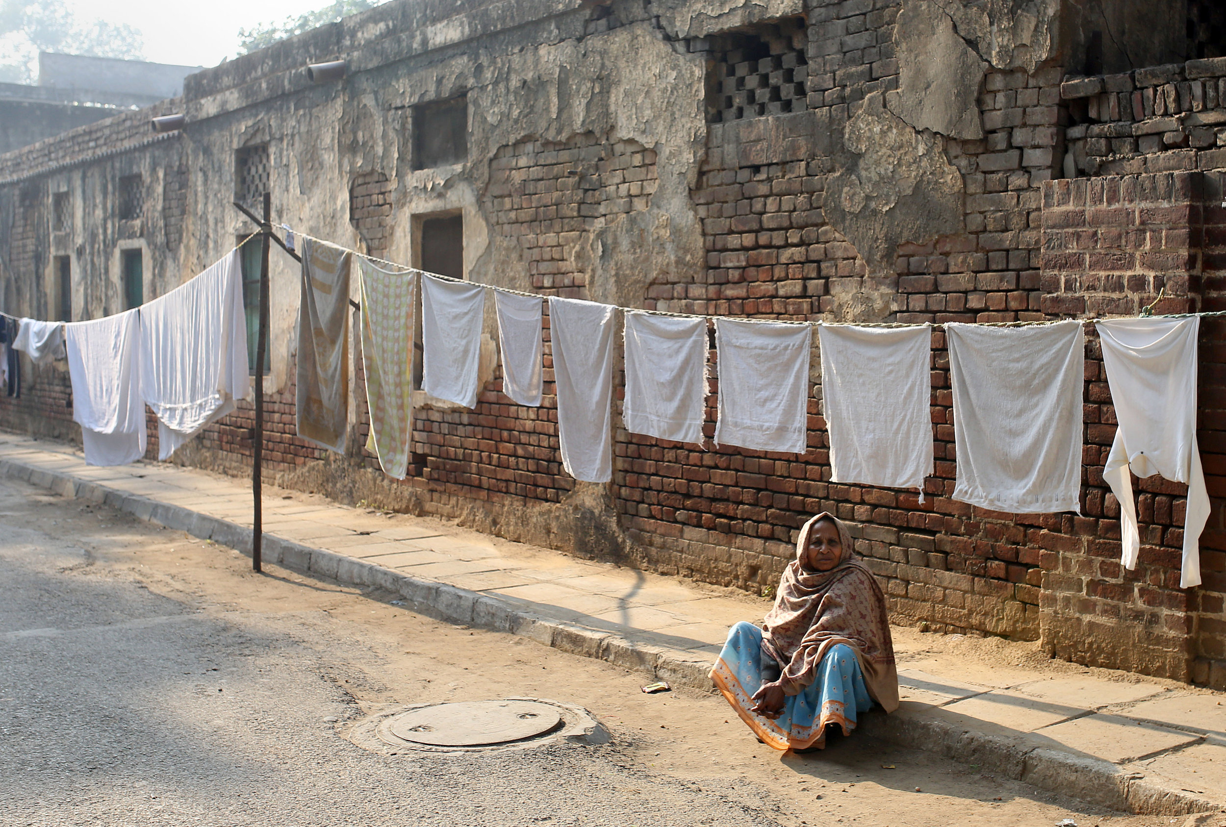An elderly woman sits among drying washing in the laundry area of New Delhi, India