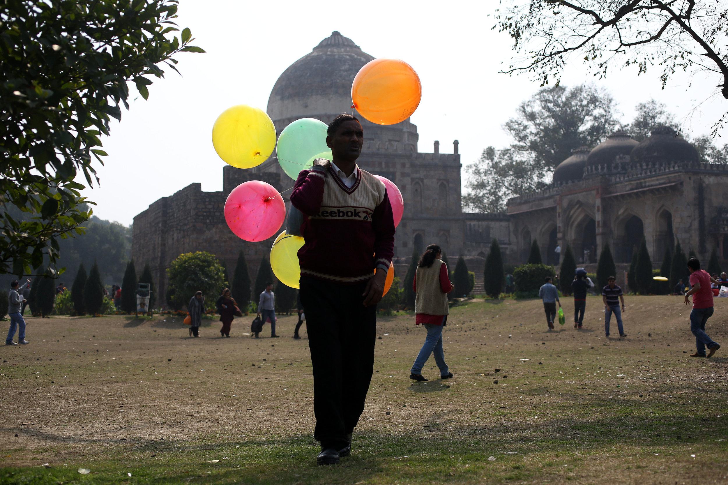 A balloon seller is pictured walking through Lodhi Gardens in New Delhi.