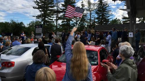 Woman waving American flag.