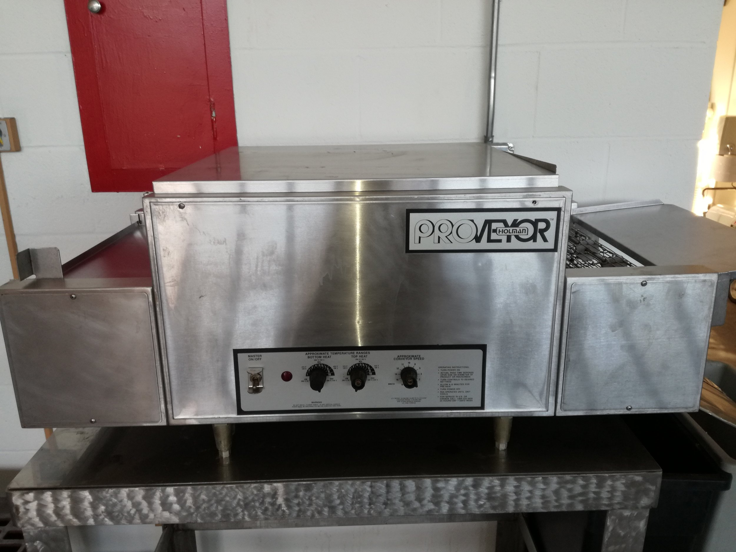 Holman Commercial PIZZA Conveyor Oven $675 - Excellent shape countertop pizza oven. These ovens are designed to cook a variety of menu items such as fresh dough pizza, blanched pizza, subs, cookies, fish and more quickly and easily while conserving cooking space. * Quartz Infrared Heaters provide faster, more consistent heating than traditional heating elements.* Dual Elements are located above and below conveyor belt allowing precise even heating of products.* Forced convection increases productivity by circulating preheated air into the cooking chamber.* Conveyor belt speed control and top and bottom heat control enables different menu items to be baked on the same oven providing superior flexibility.* Ovens can be stacked one, two or three high with our stacking spacer to conserve cooking space.*Production: 10-12 16