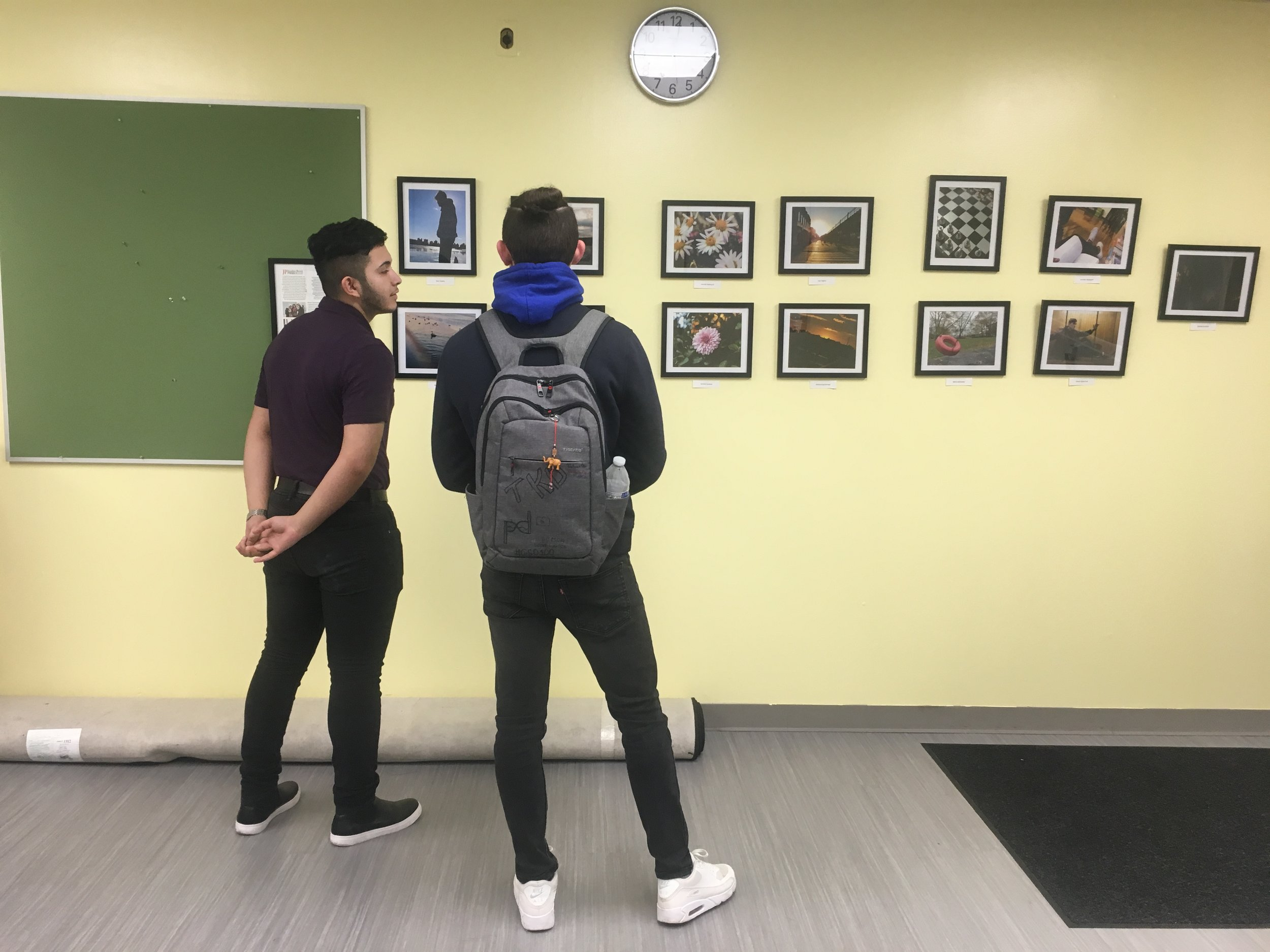 Uriel (left) speaking with one of the student photographers at the exhibition for the International High School at Lafayette on February 7, 2019.