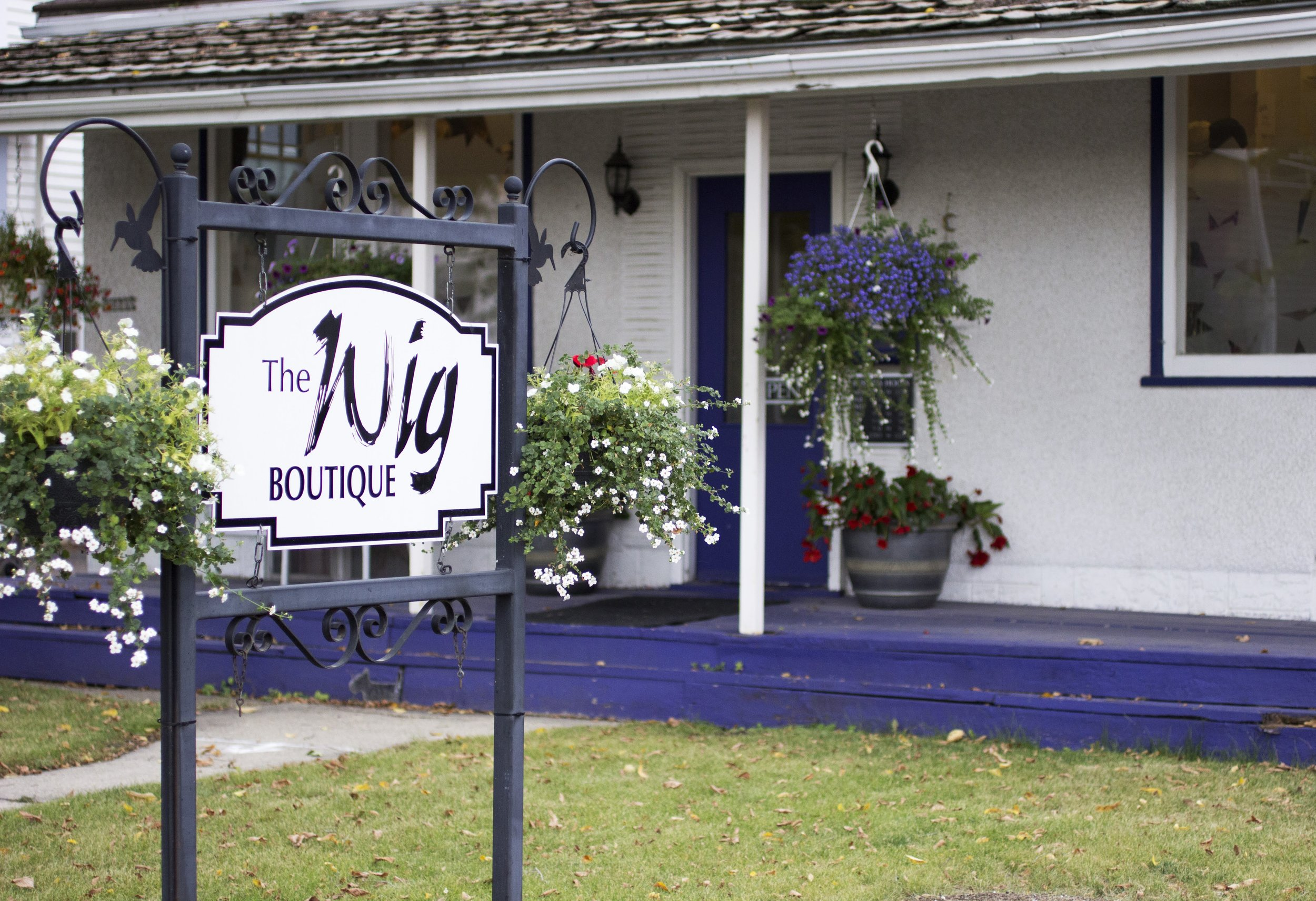 The outside of the shop. The Wig Boutique is inside a white house with a purple porch and door. There is a sign on the front yard.