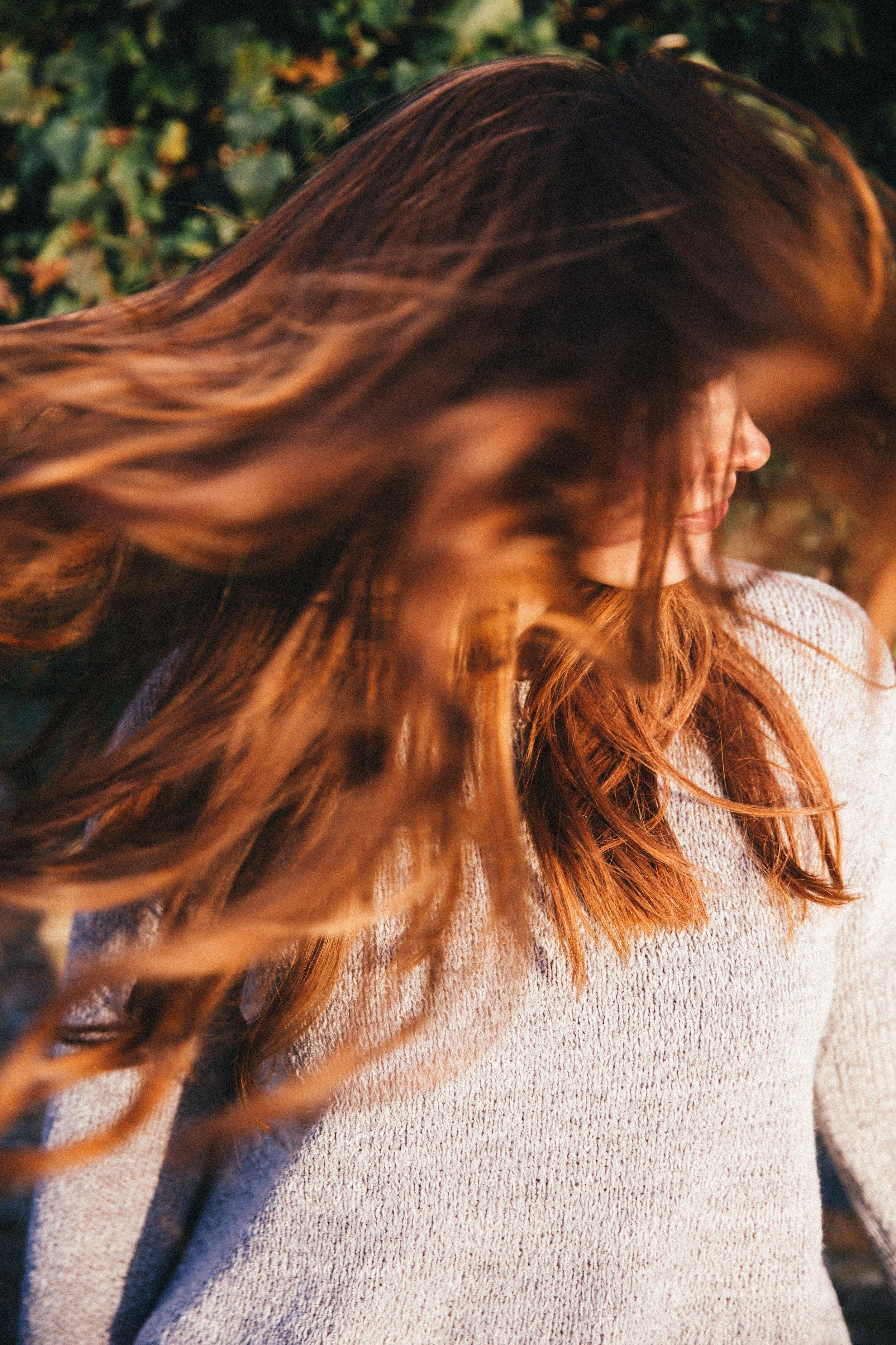 A girl twirling her long brunette hair.