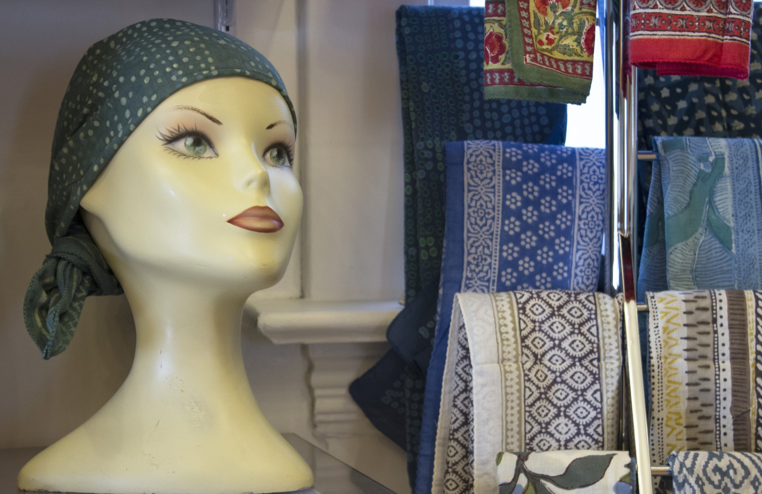 A plastic mannequin head displaying a scarf, with more scarfs hanging next to it. From the headcoverings section at The Wig Boutique.