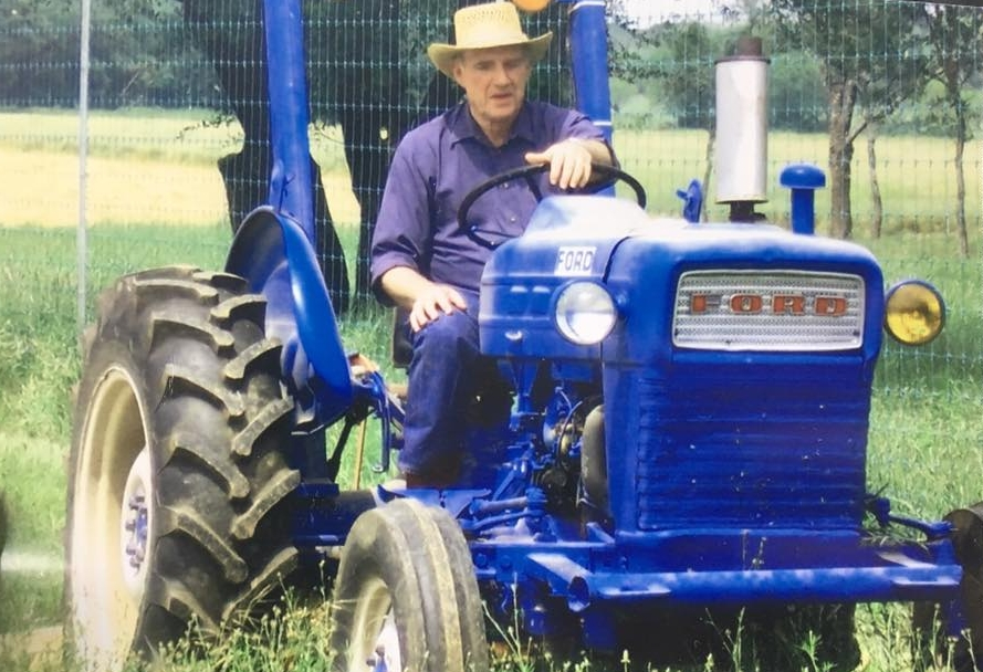 Pop riding his beloved tractor at the ranch.