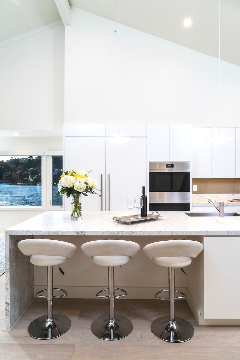 The Top of The Pointe kitchen, a dream for those who enjoy entertaining, was designed with spacious custom cabinetry and storage, an expansive kitchen island, Carrara marble slab island and countertops, and honed quartz backsplash.