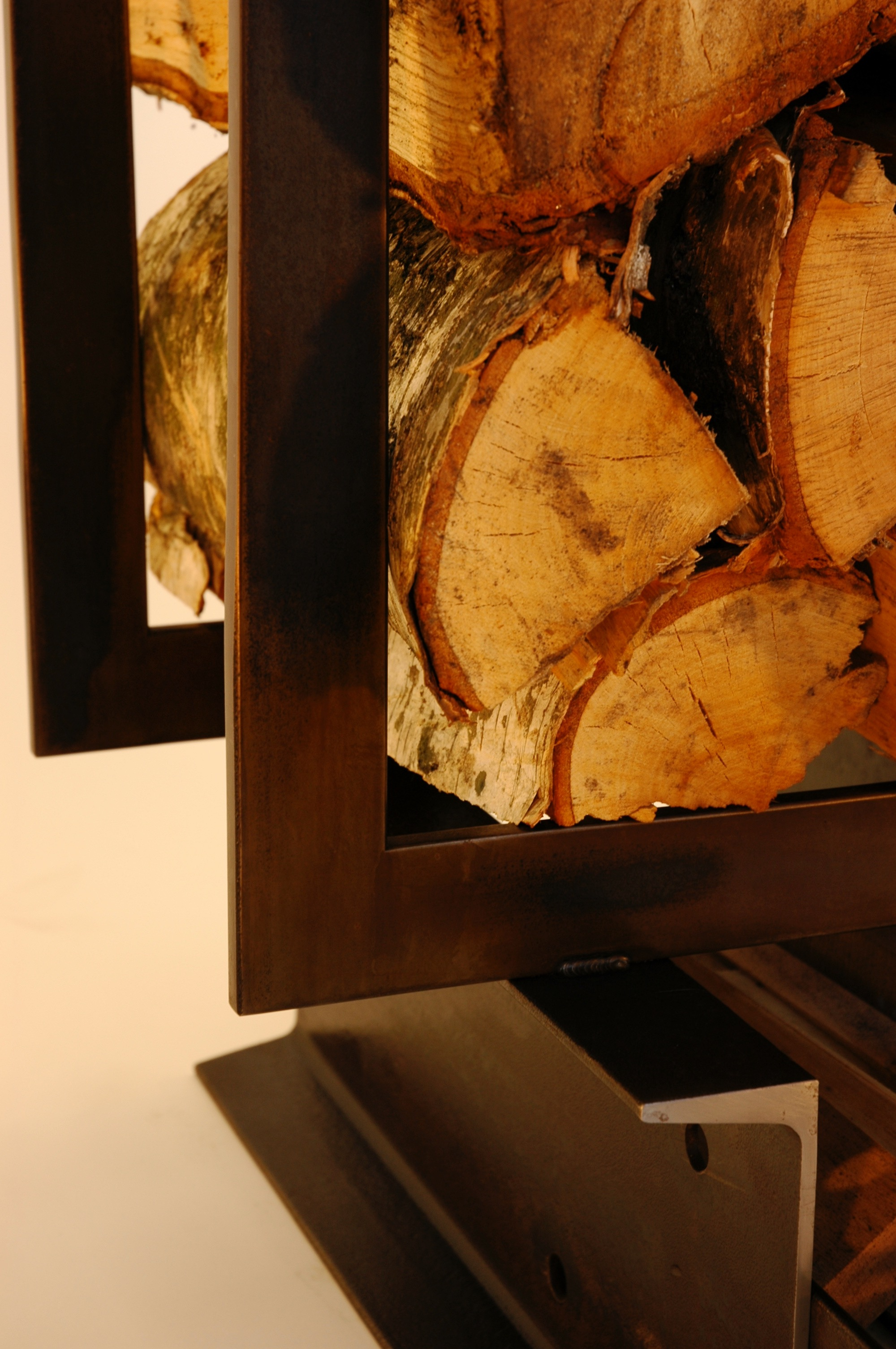 """LOG TRUCK: This wood and kindling holder was fabricated from hot rolled steel flat bar and """"C"""" channel. Brown/black patina."""