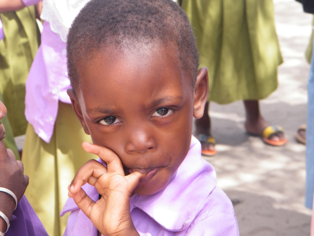 A young male student wearing a purple shirt, with his finger in his mouth!