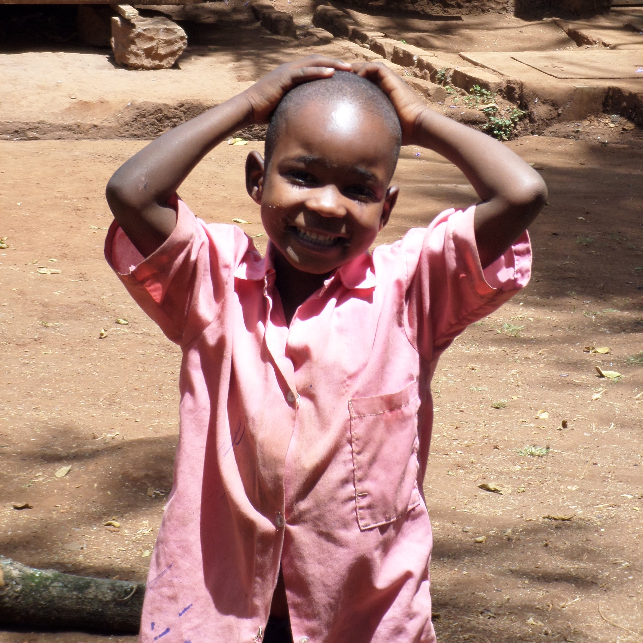 Kenyan boy in a pink shirt with his hands on his head, representing child advocacy.