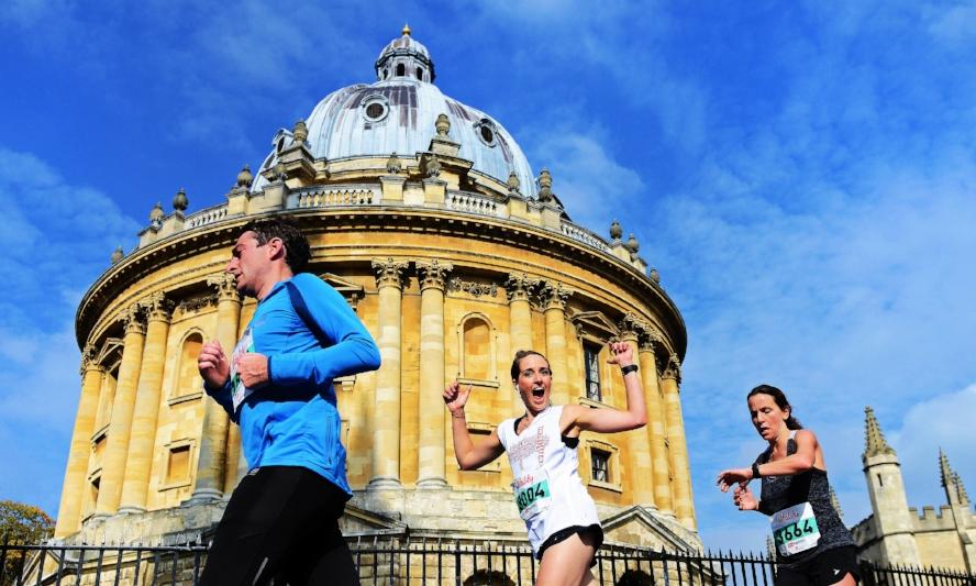A happy African Children's Fund half marathon runner, passing the Radcliffe Camera in Oxford in sunshine.