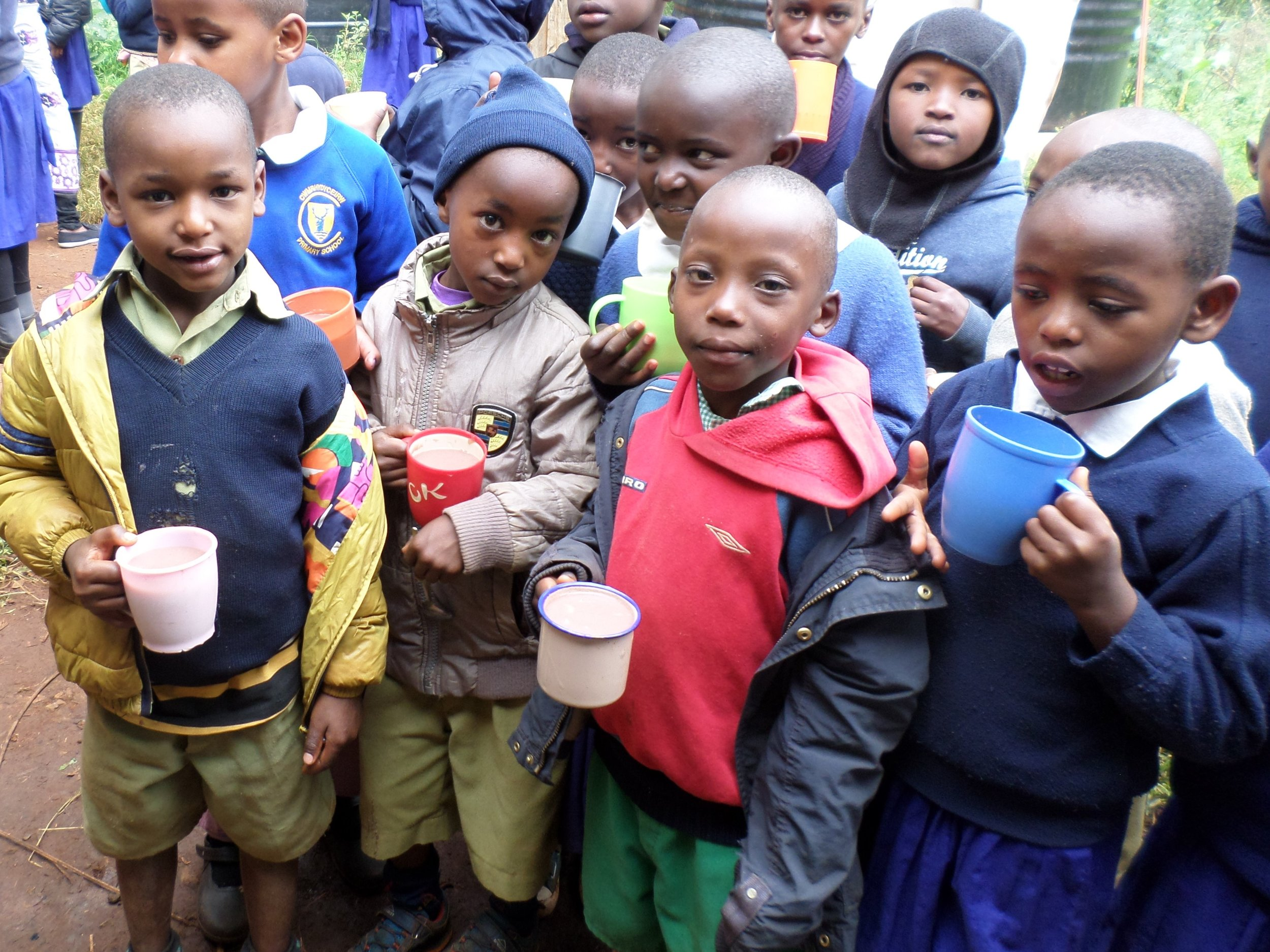 4 children wearing coats and holding mugs of porridge from their school Porridge Club.