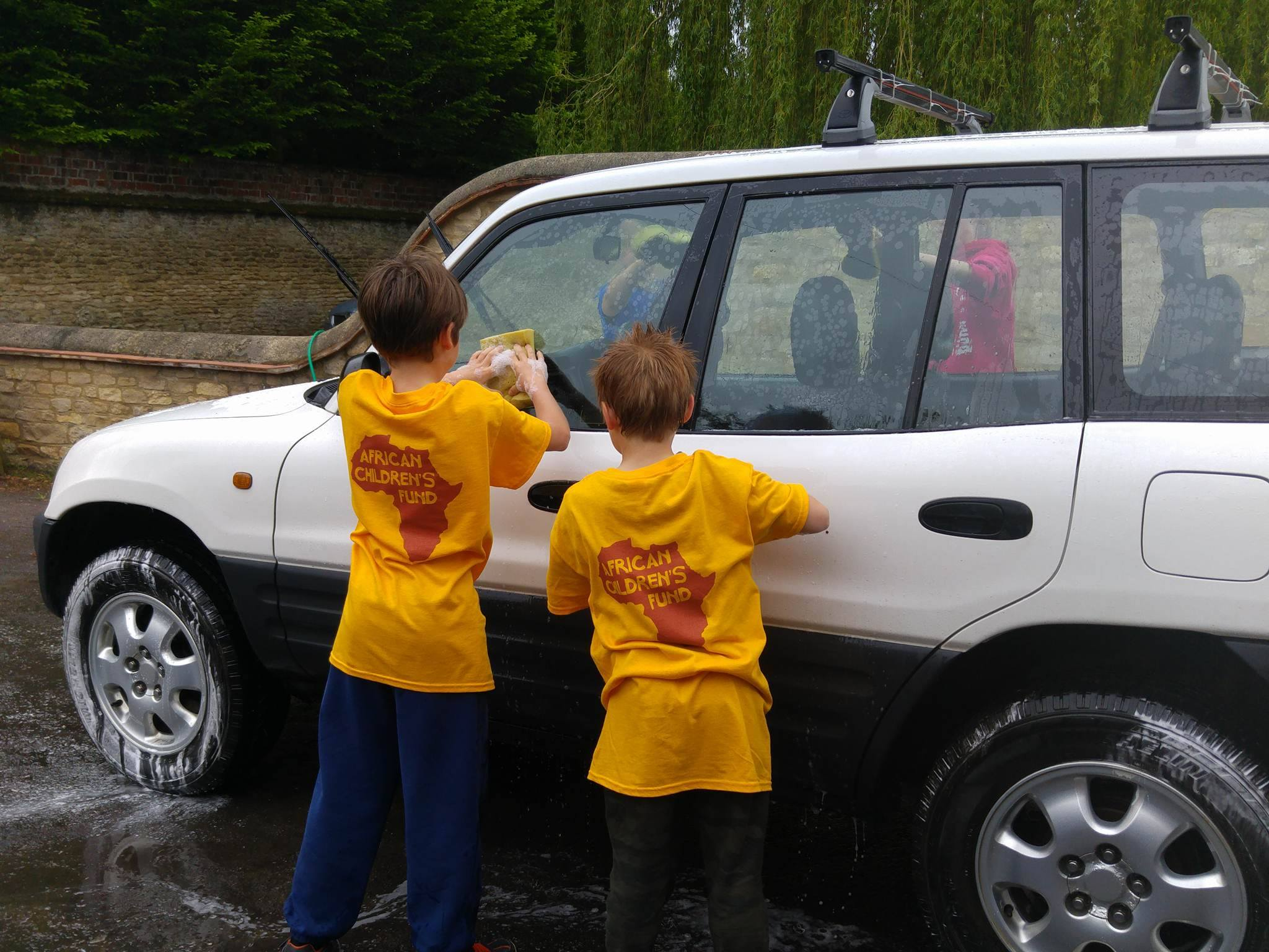 2 youngsters wearing yellow African Children's Fund t-shirts, washing a white car.