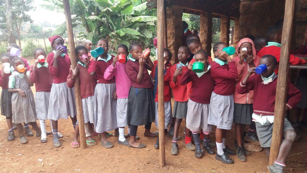 A queue of Kenyan primary schoolchildren wearing burgundy school uniforms, drinking mugs of porridge under an external wooden structure.
