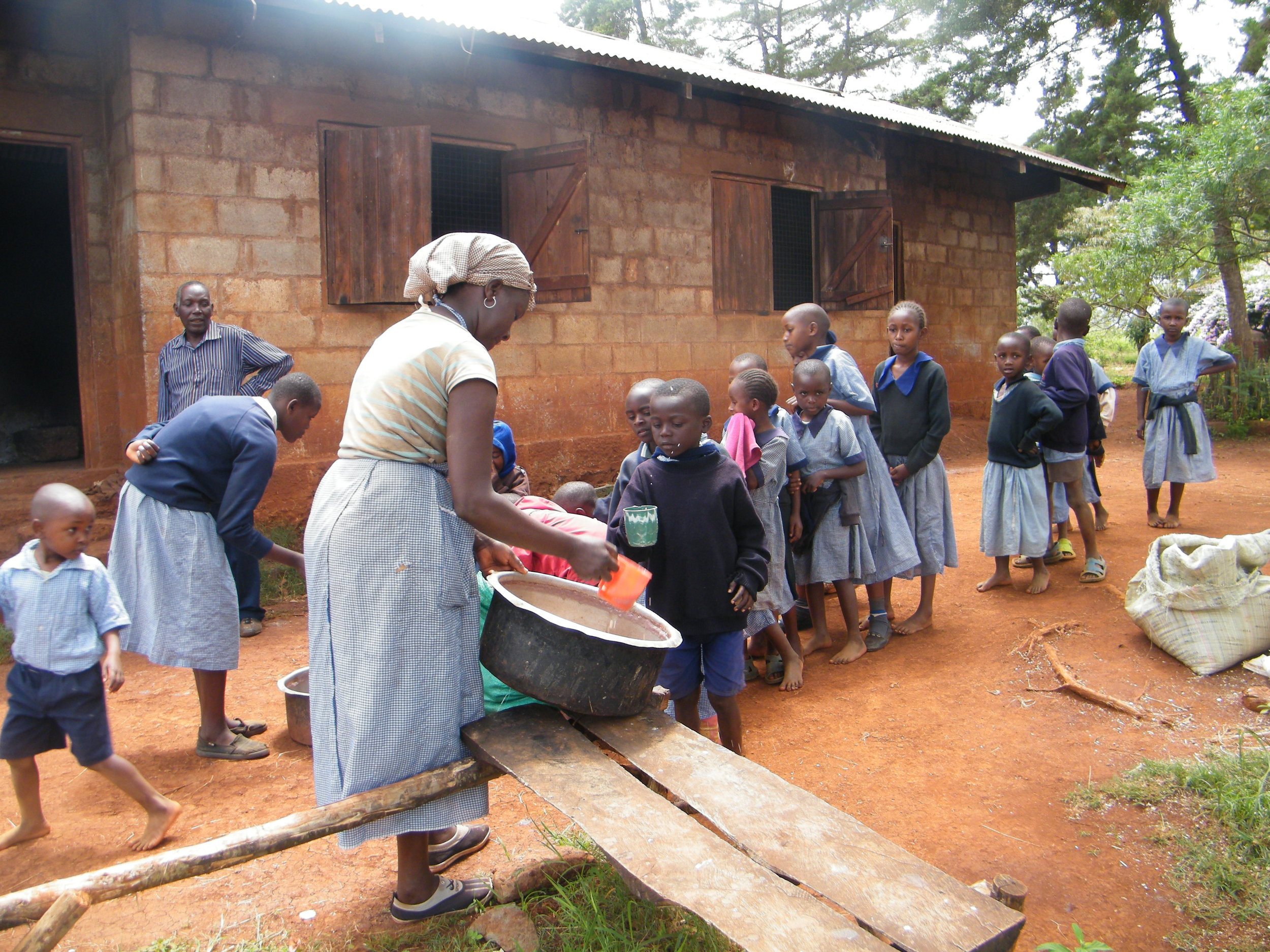 Kenyan children in blue uniforms queuing for porridge being served by a school cook.
