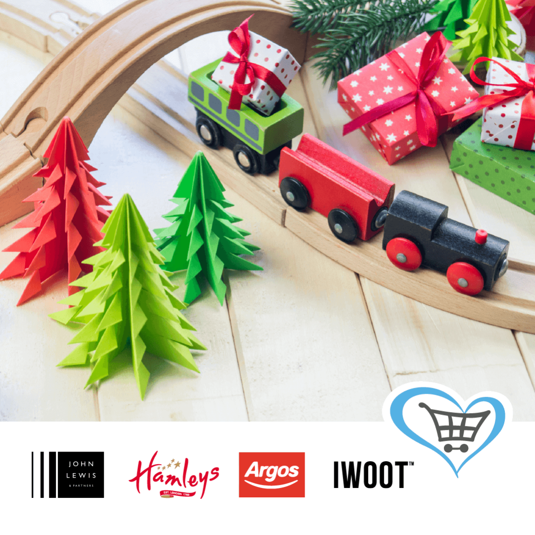 A wooden train set with small gift wrapped presents beside it and paper Christmas trees. Logos of Give As You Live and some of their stores appear underneath.