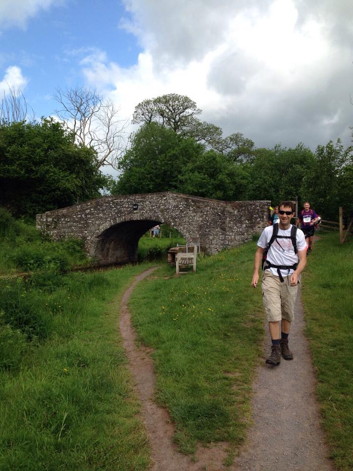 A fundraiser taking on TrekFest for African Children's Fund, in front of a stone bridge & wearing a rucksack.