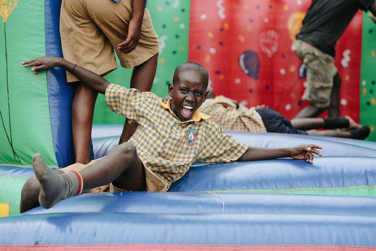 4 Ugandan children having fun on a blue & green bouncy castle.
