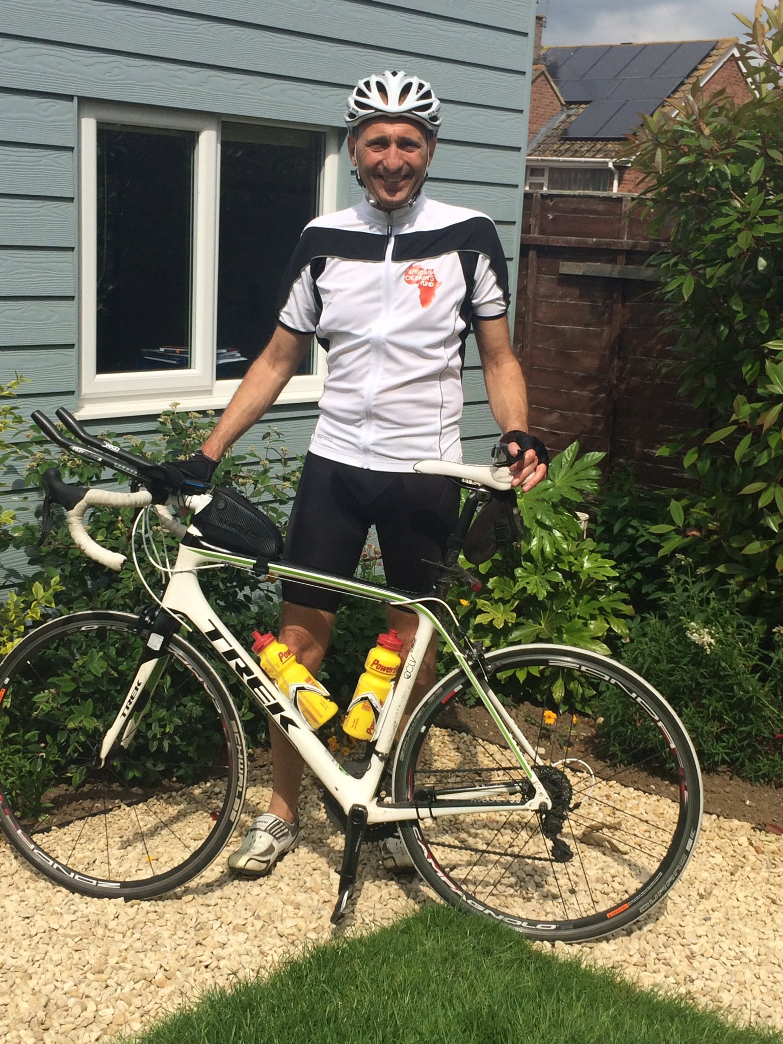 Steve standing behind a white, Trek bicycle wearing a white & black cycling jersey that also includes the African Children's Fund logo.