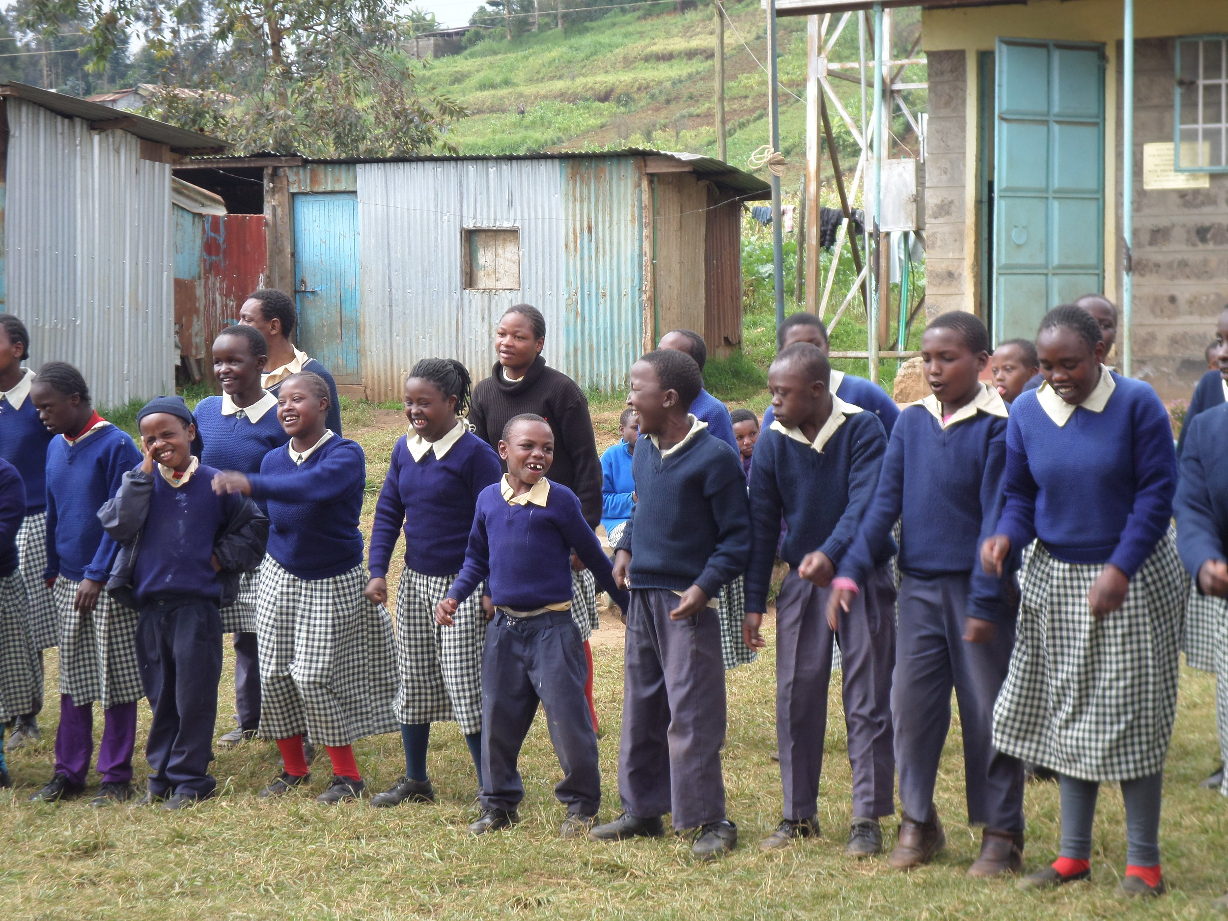 A row of pupils from AIC Mukeu School wearing green uniforms, dancing on grass outside school buildings.