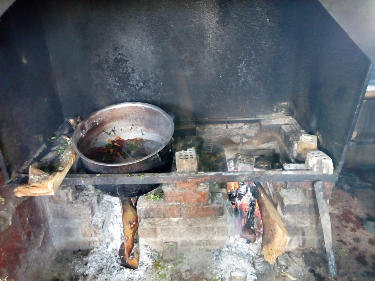 The current cooker is an open fire with a metal frame above it with pots standing on it, within a brick fireplace.