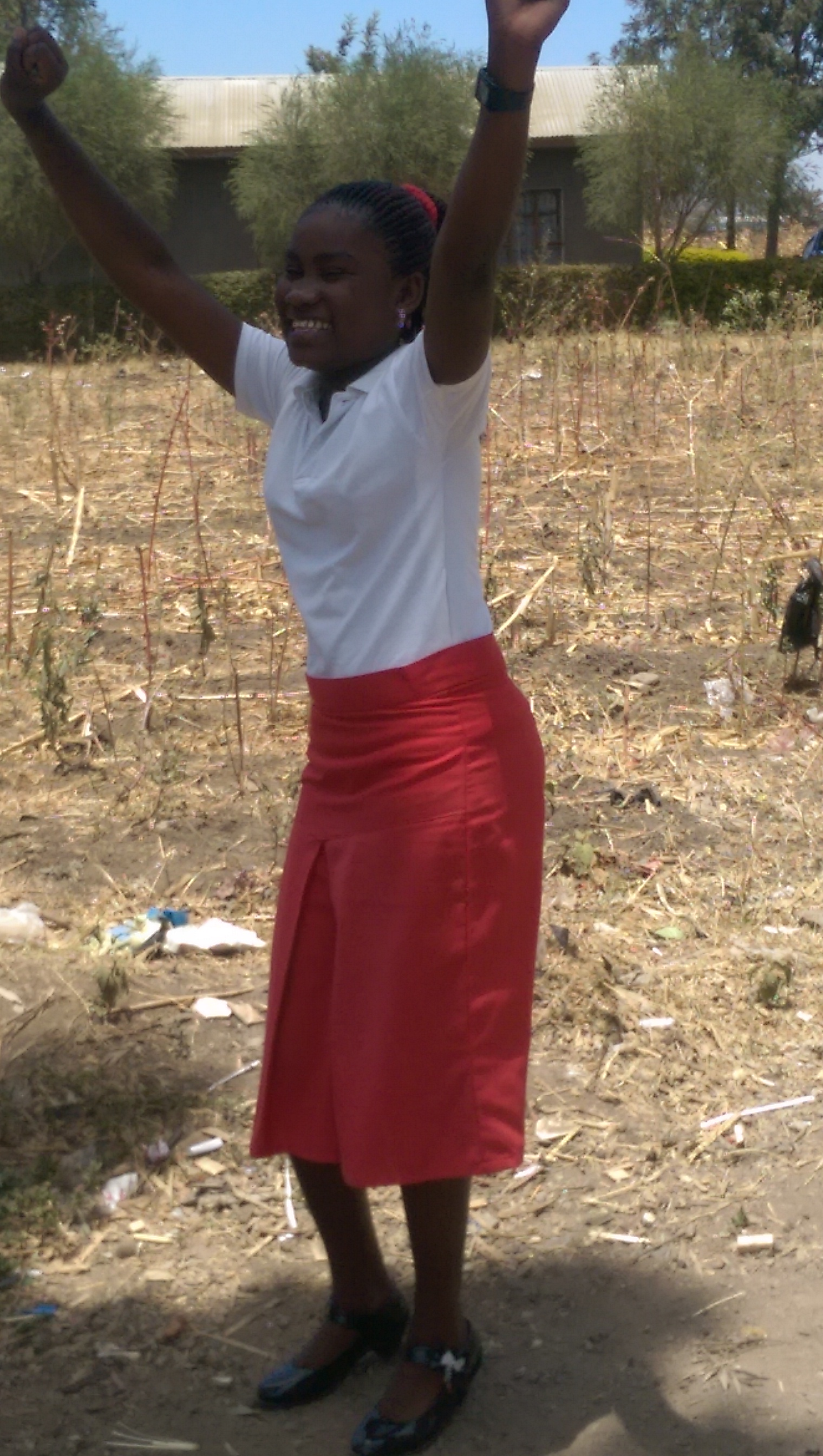 A Tanzanian girl wearing a red skirt and a white blouse, in a celebratory pose with her arms in the air.