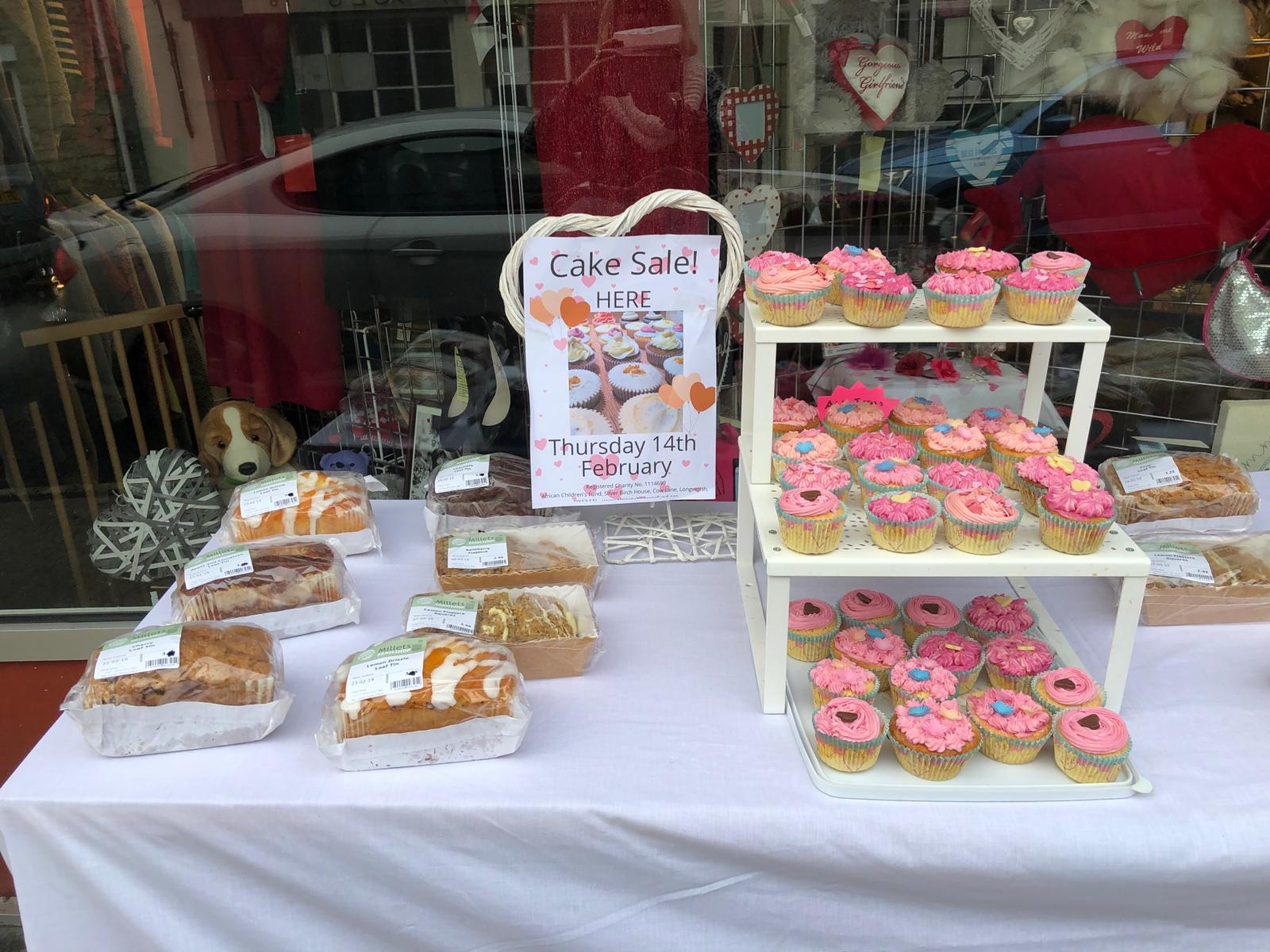 A table with loaf cakes and a display of pink-iced cupcakes on it.