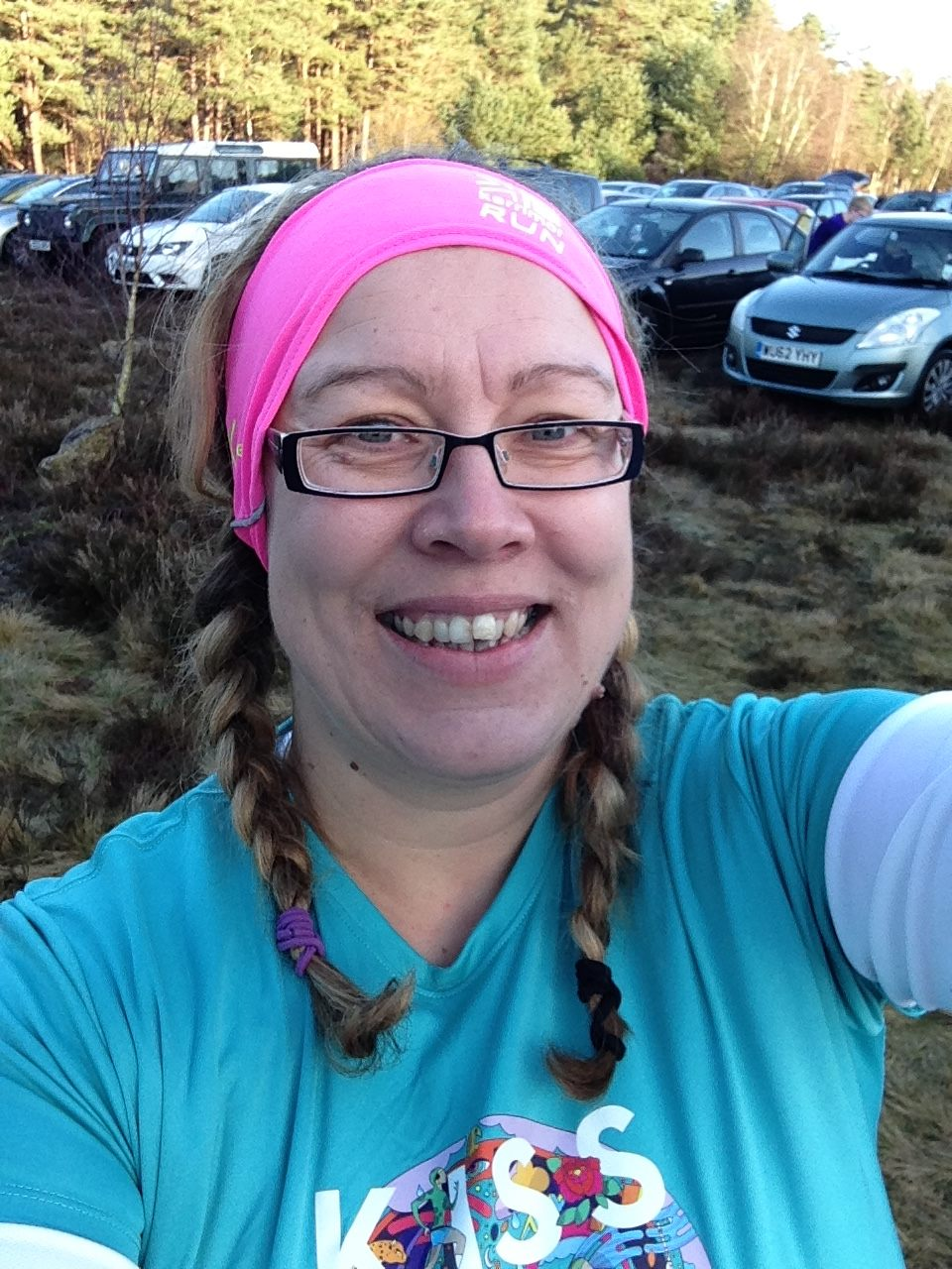 Our RideLondon fundraiser, Kellie Peters, wearing a pink headband and blue t-shirt, with plaits in her hair.